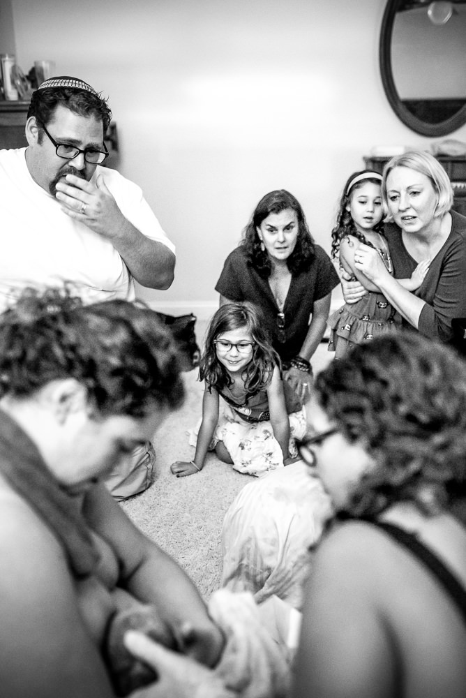 black and white photo of family reacting as they find out new baby is a girl.jpg