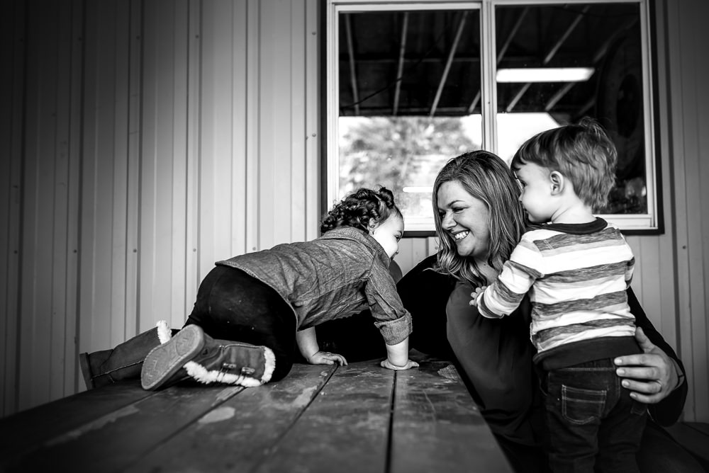 mom and her twins on a picnic table during a pumpkin patch photo shoot.jpg