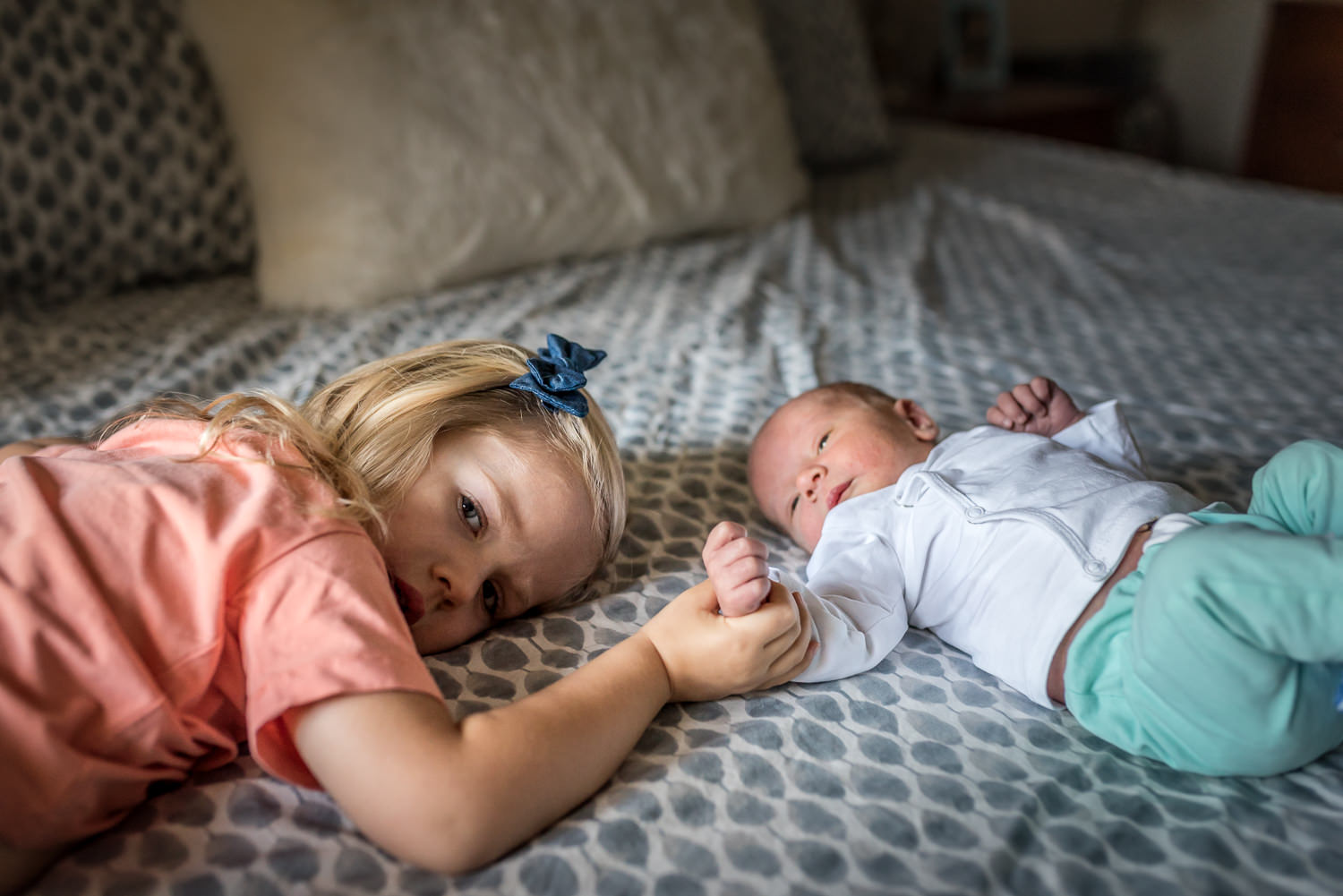 big-sister-and-brand-new-baby-brother-hold-hands-at-in-home-fresh-48-session-in-Creve-Couer-Missouri
