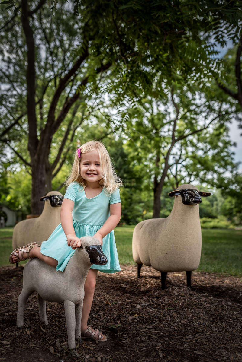 Little girl climbs on sheep sculpture at the botanical gardens in St. Louis, MO.