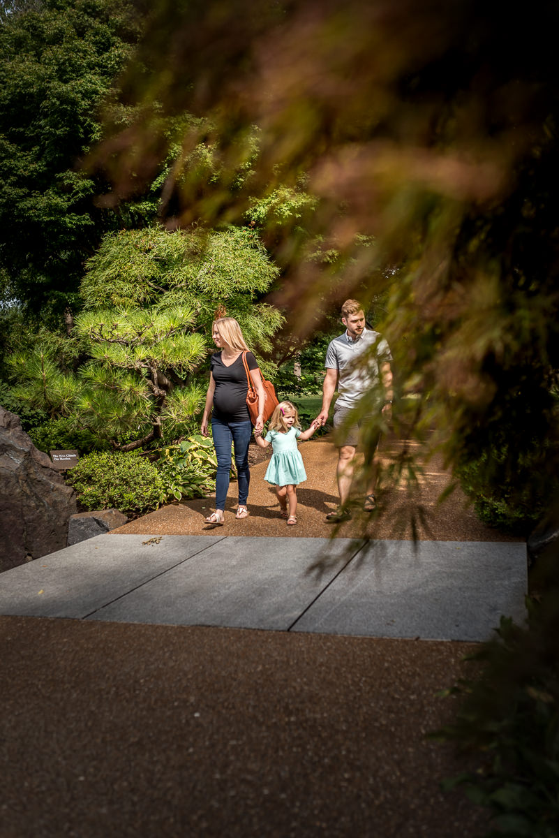 expecting mama goes for a walk with her husband and daughter on a summer day at Missouri botanical gardens.