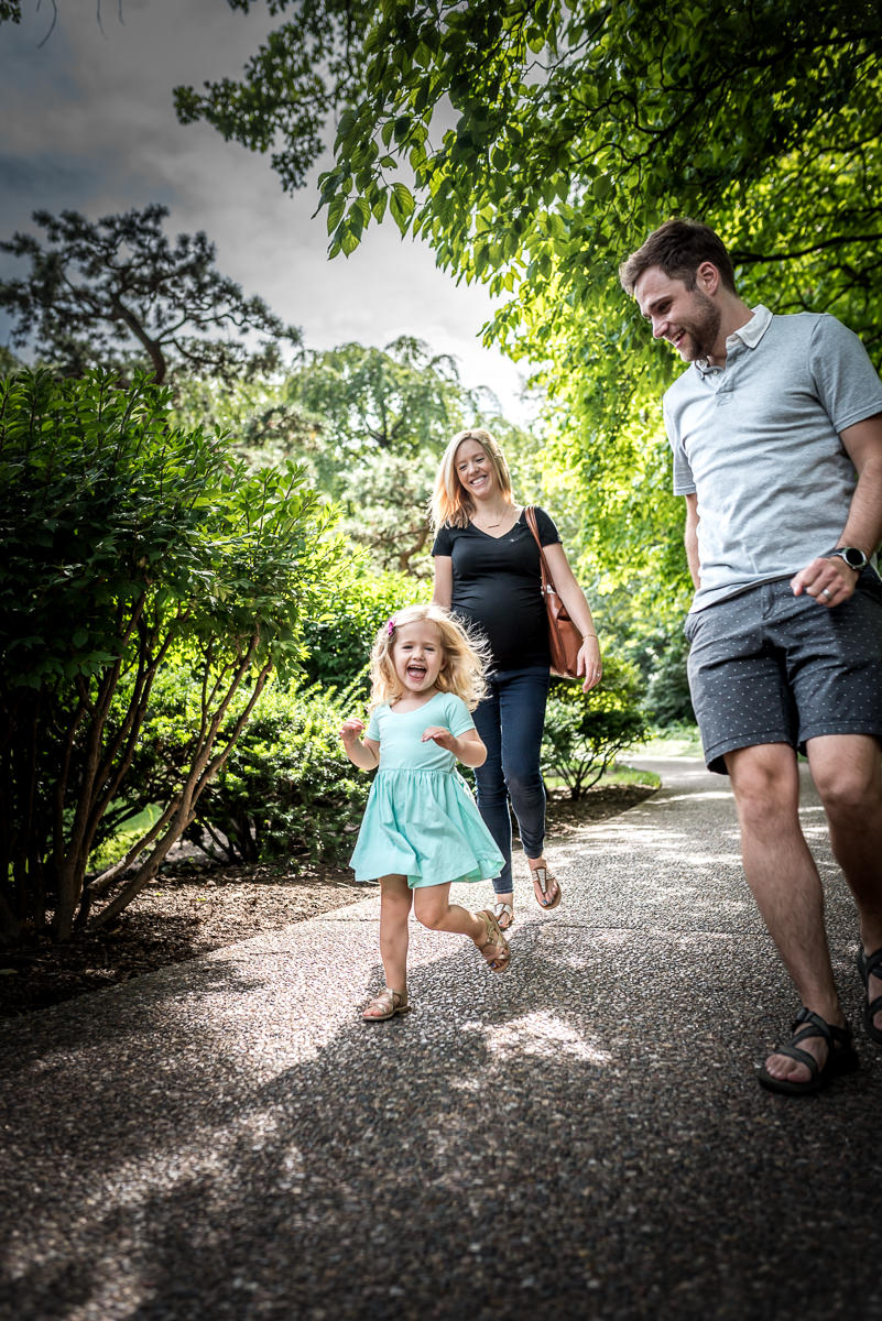 Little girl running down a path with her parents chasing after her.