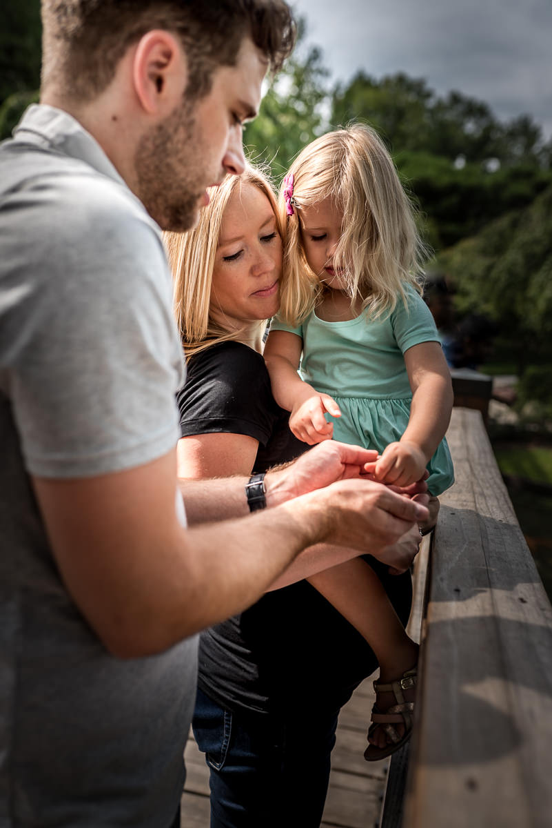 mom and dad help daughter feed the fish at Missouri Botanical Gardens.