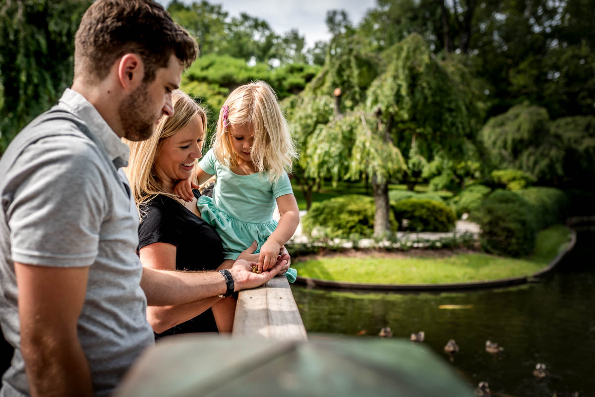 family feeds the fish at MO Botanical Gardens on a sunny day.