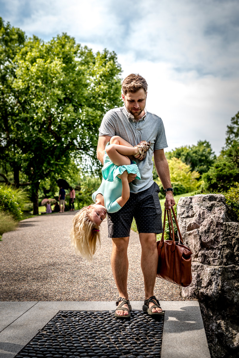 Dad carries wife's purse and giggling daughter upside down.