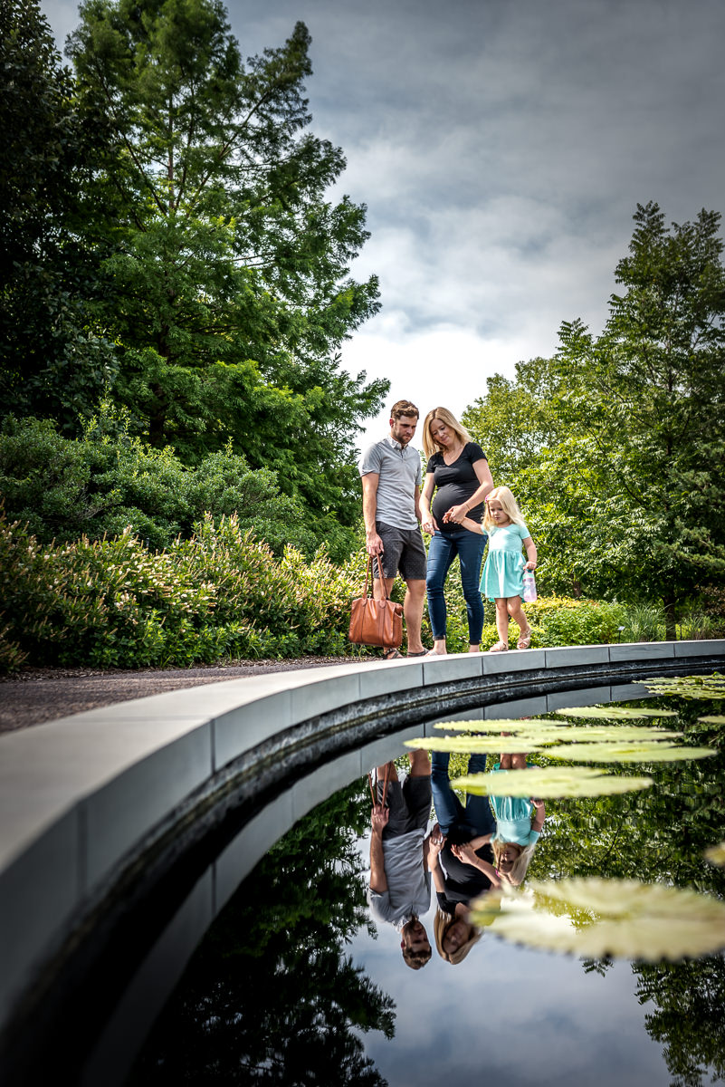 Baby bump surrounded by family and nature at MO Botanical Gardens in St Louis.