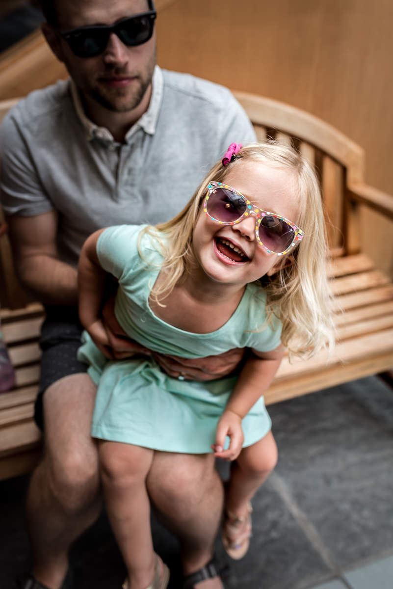 This little girl is so cool she wears her sunglasses inside.