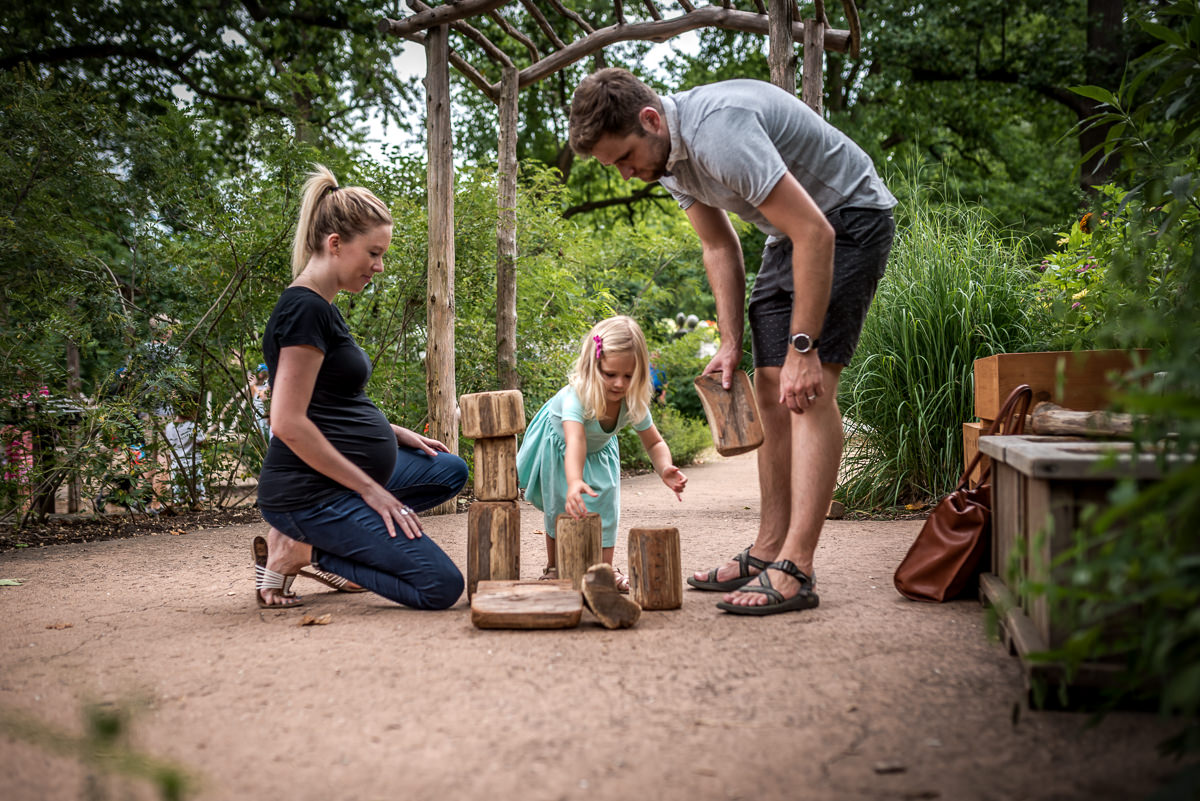 pregnant mom and dad enjoy watching daughter build with natural wooden blocks at MOBOT in St. Louis