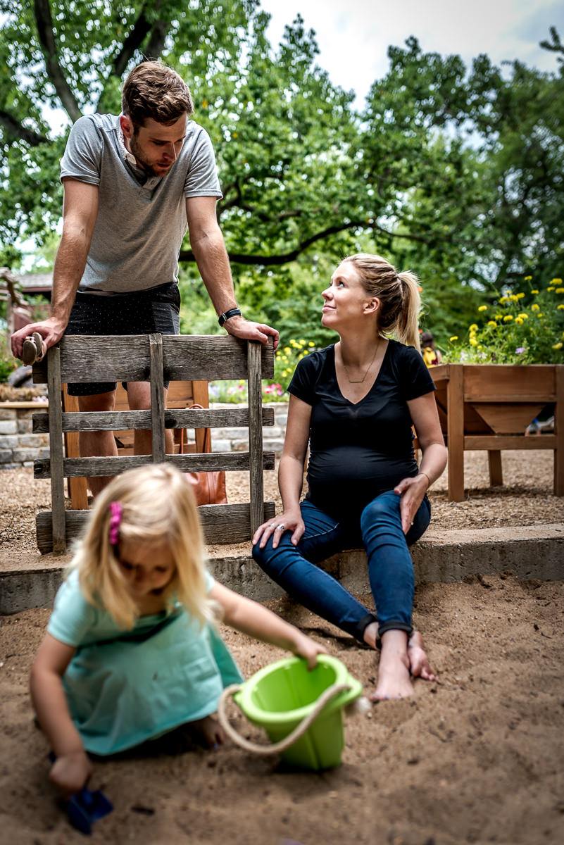 pregnant mom puts her feet in the sandbox while her older daughter plays nearby.