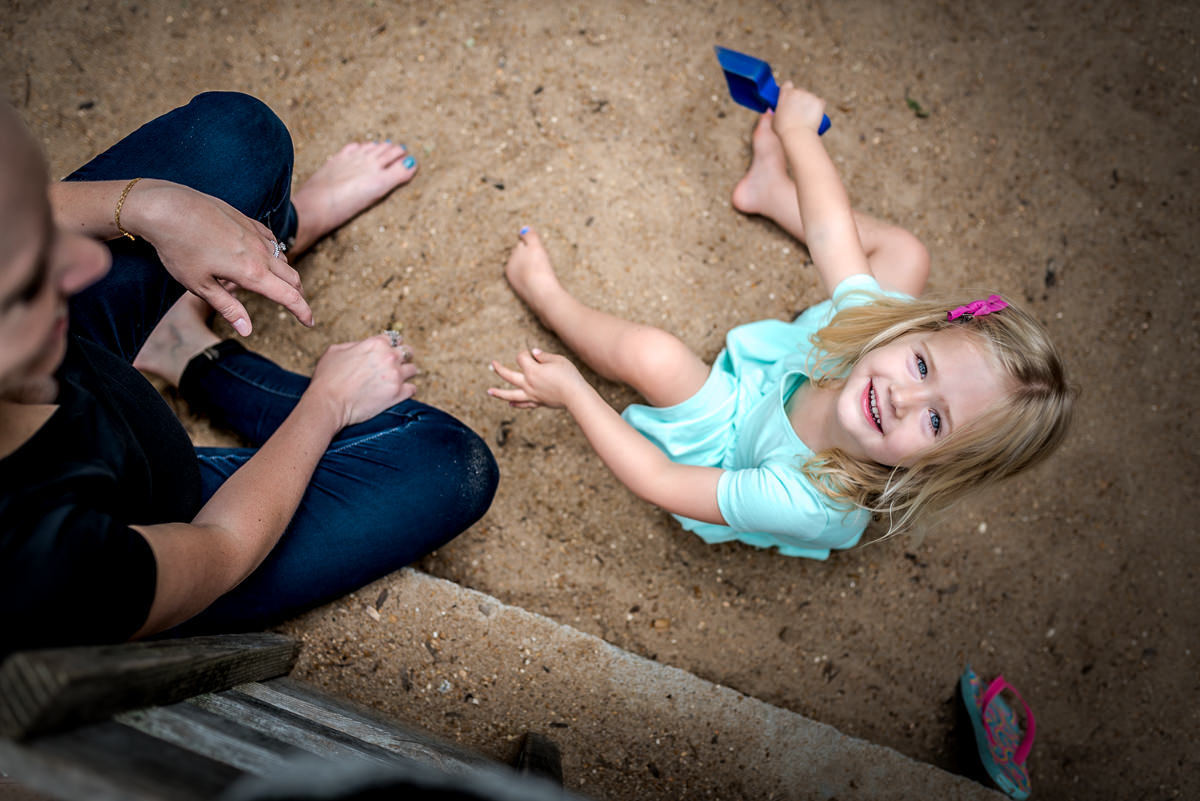 mom and daughter play in the sand together during a photo shoot.