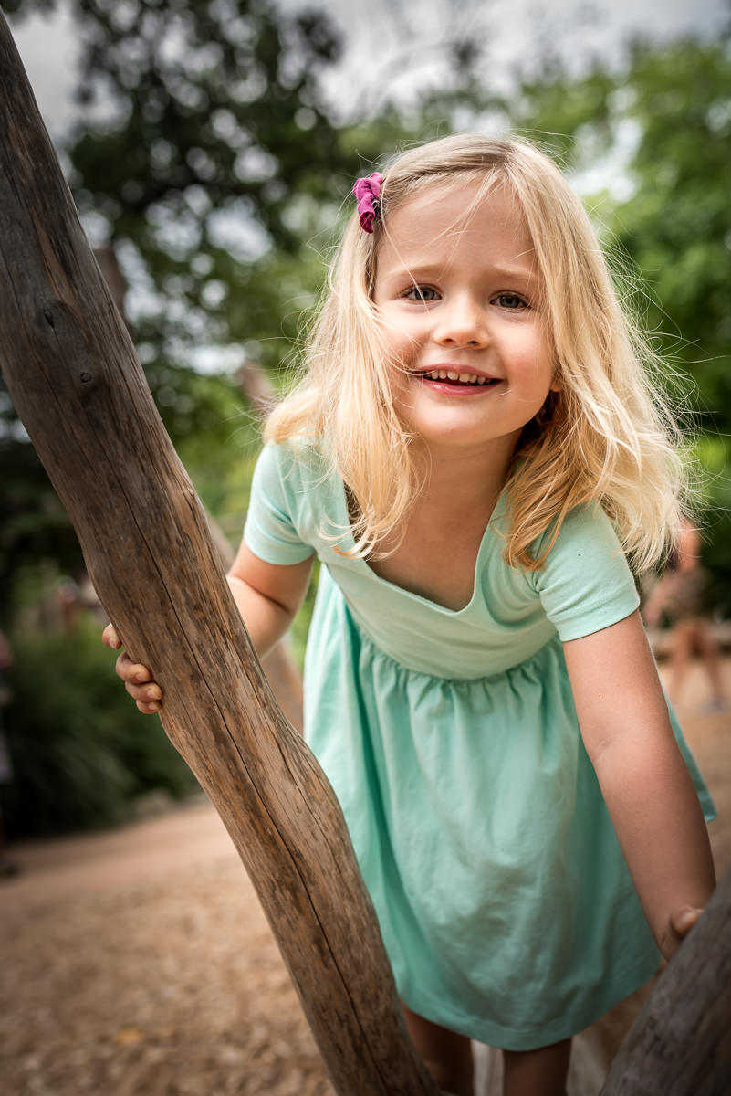 toddler climbs and plays on wooden log during a documentary photo session at Missouri Botanical Gardens in St. Louis.