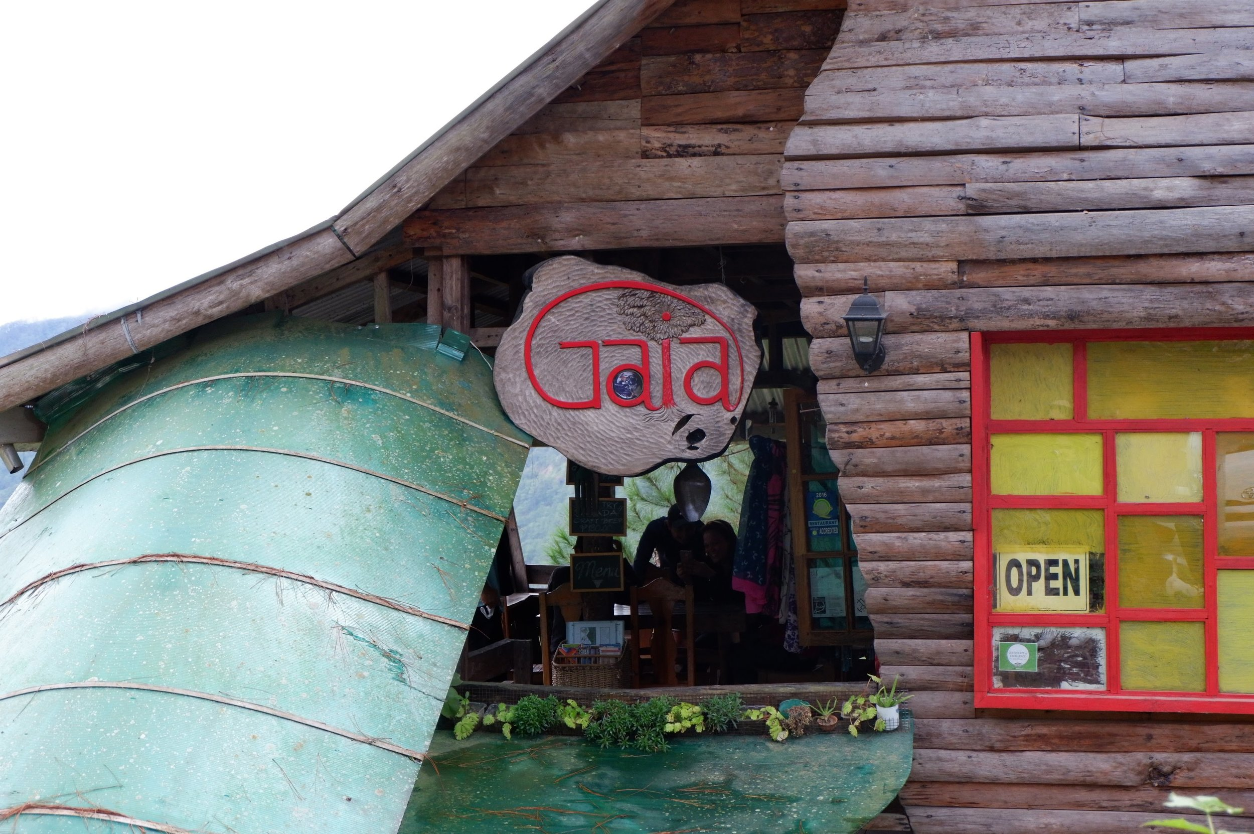 """GAIA CAFE - A community-based Kankanaey cafe by Gawani in Ambasing, Sagada. Its tree-house-inspired cafe made from repurposed wood is located on a cliff with a 270-degree view of the valley on the way to Sumaguing Cave.The name means """"Mother Earth"""" in Greek, and they serve organic, community-sourced ingredients from around Sagada.The menu is mostly vegetarian, but not limited to it."""