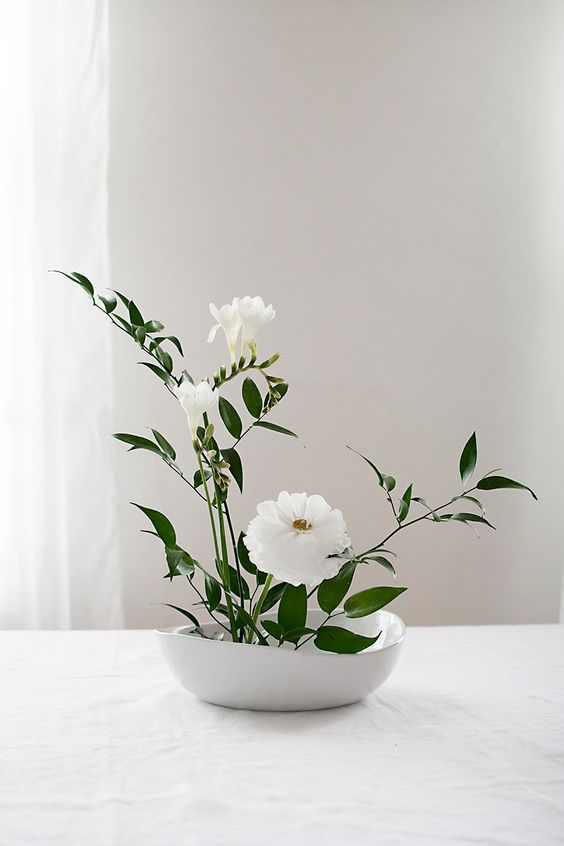 A beautiful, light,  minimal floral arrangement  creates a pleasing pop of greenery while maintaining a clean aesthetic.