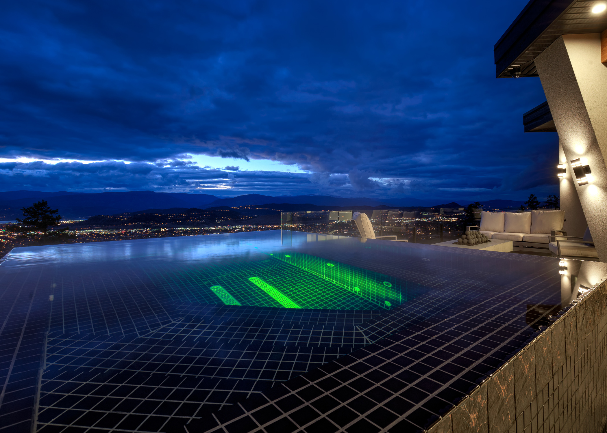 dramatic image of infinity pool lit up at night