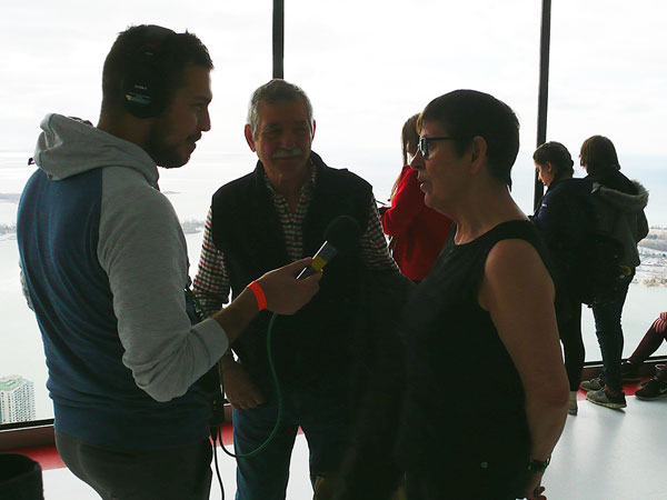 Interviewing Fatima Hrienko (right) and her husband Nick Hrienko (middle) at the top of the CN Tower following Fatima's climb.