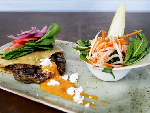 BimBeriBon's grass fed lamb pita burger with lettuce, tomato, onion, house pickle, feta and faba harissa aioli.(Photo: Angela Wilhelm/awilhelm@citizen-times.com)