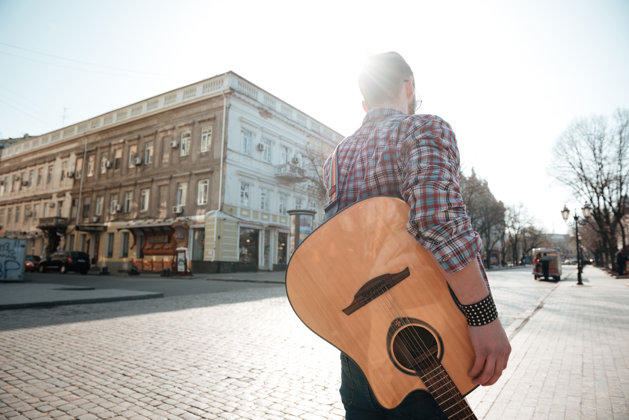 man-walking-with-guitar-outdoors-P66N2F7.jpg
