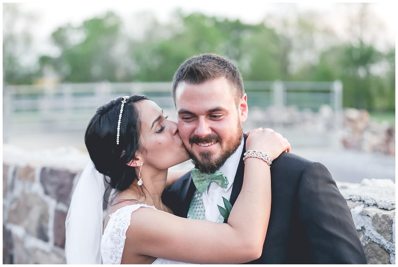 bride kisses groom on cheek