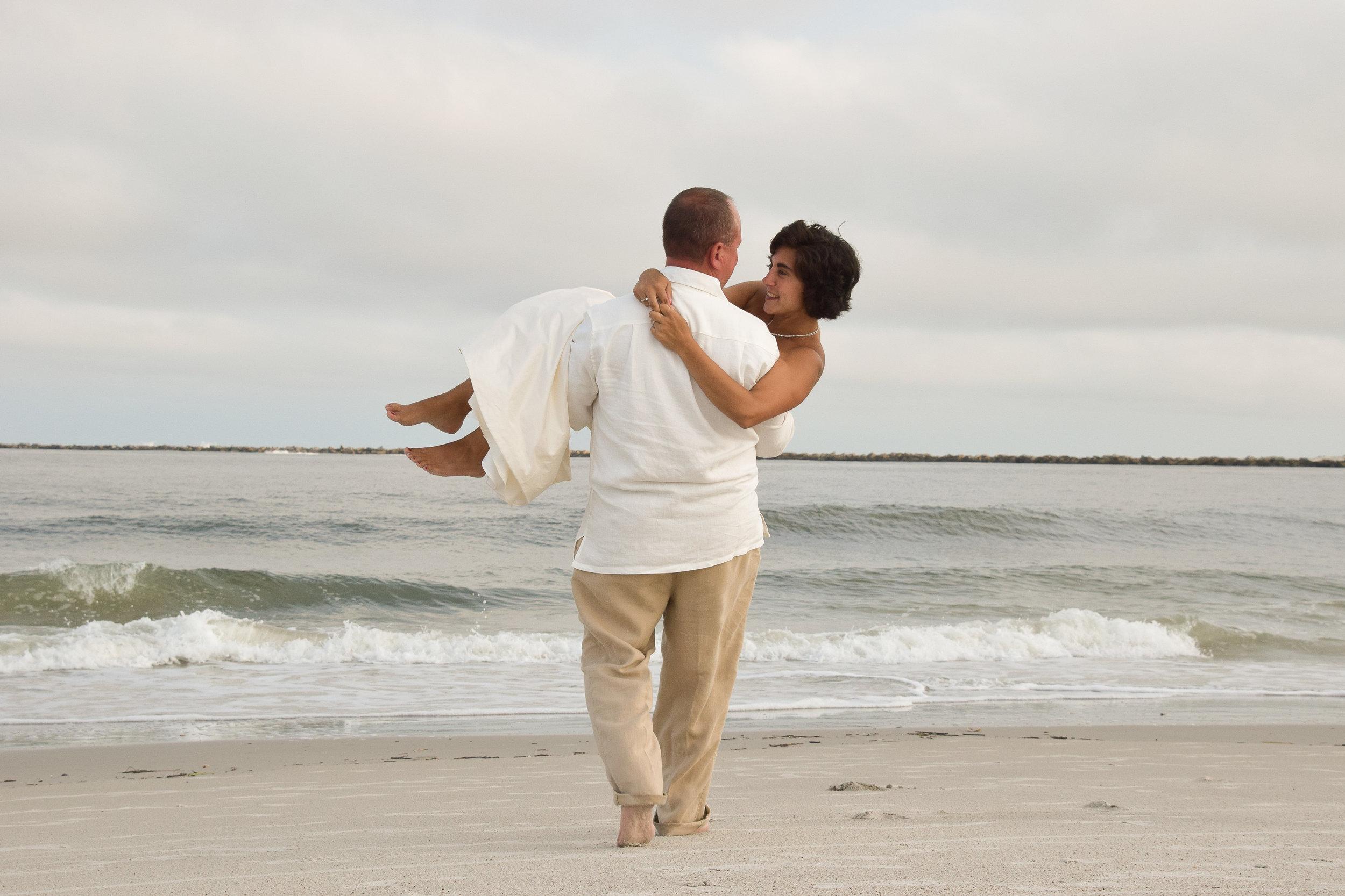Groom carrying his bride towards the Ocean.