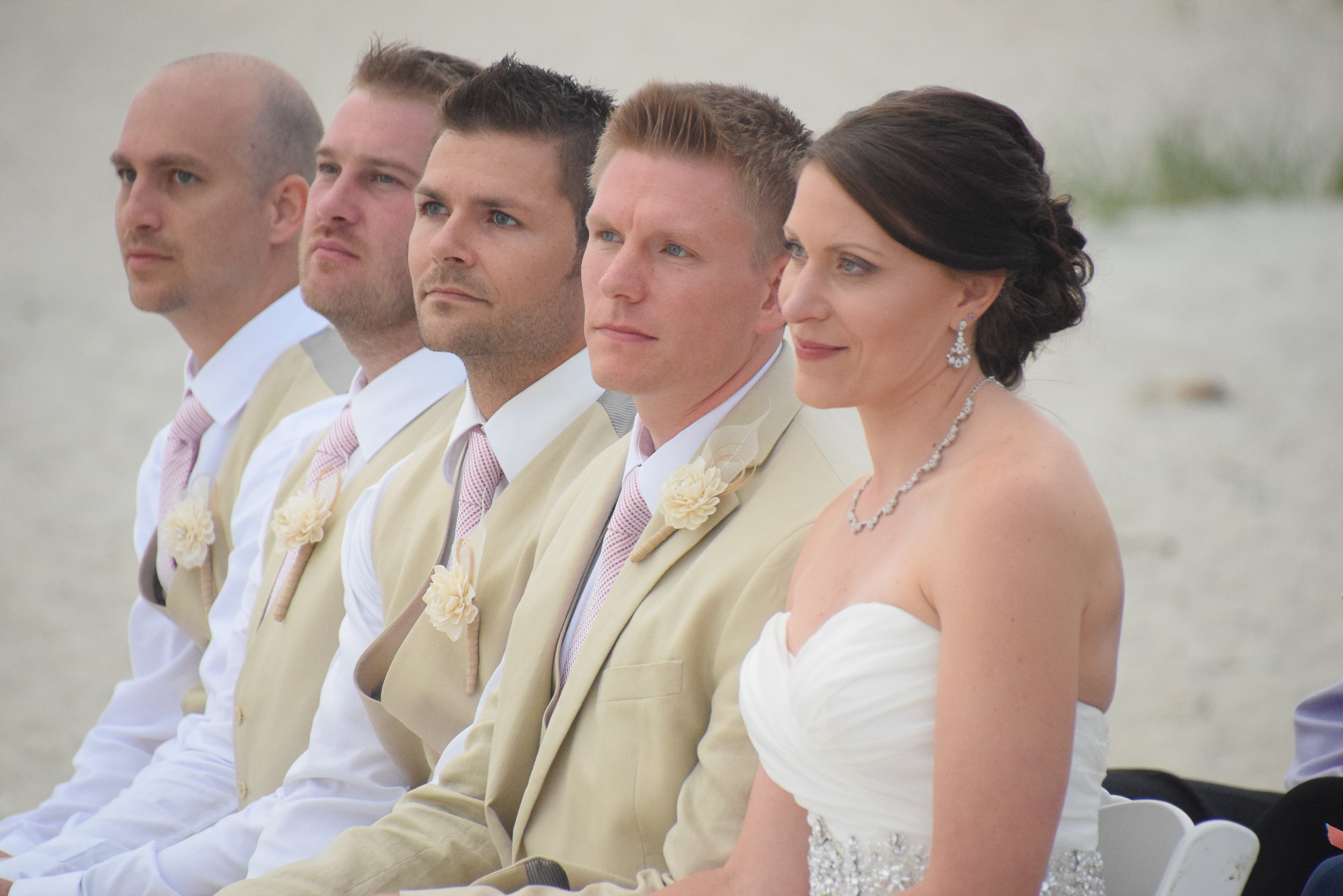 Bride and groom listening to ceremony with attendants.