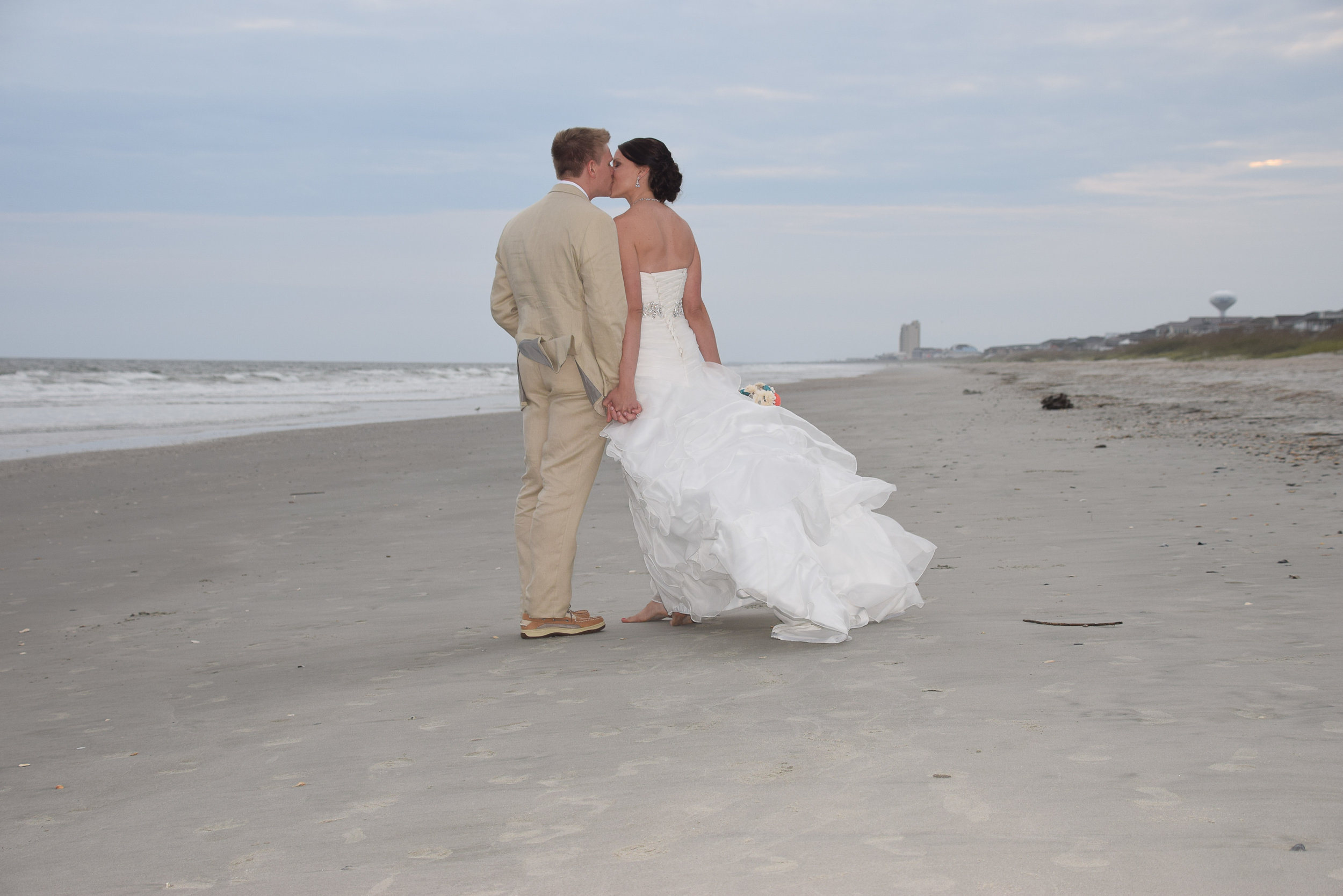 Bride and groom walking and kissing.