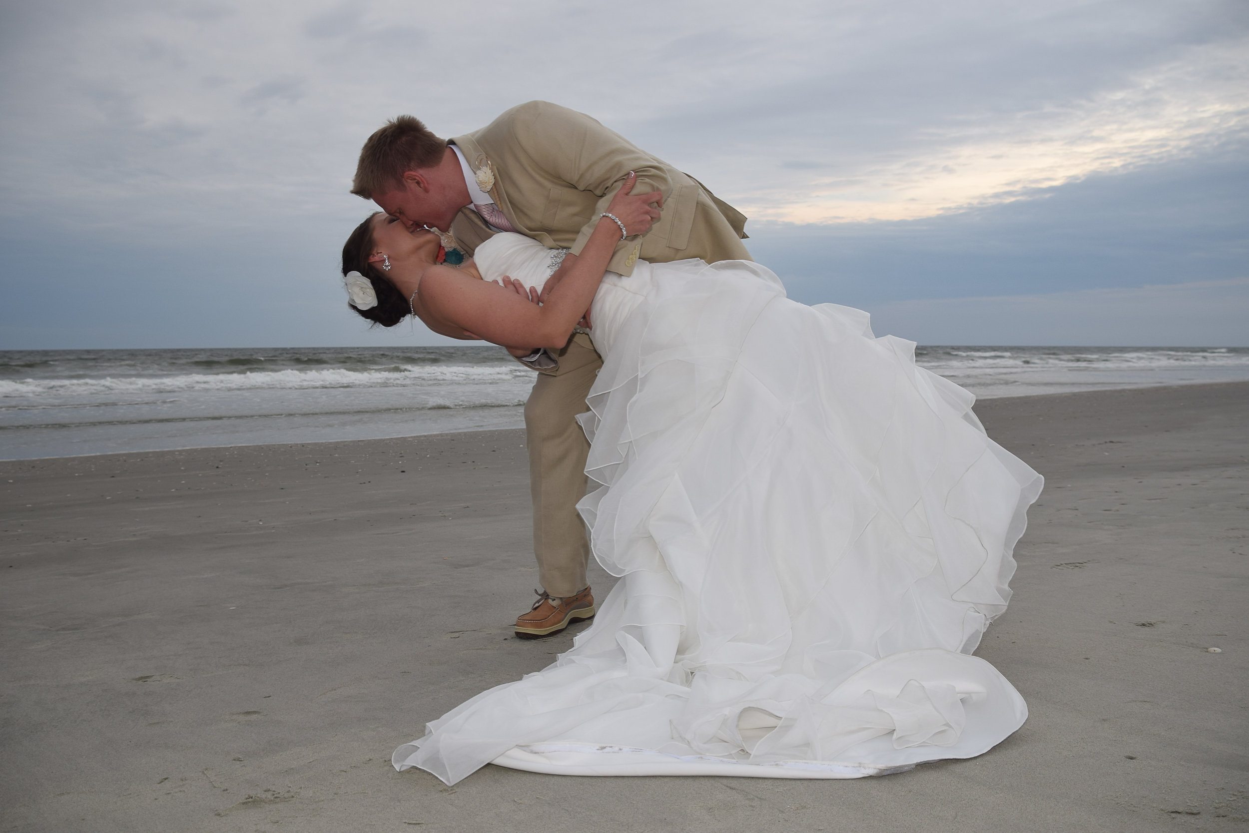 Groom dipping his bride on the beach.
