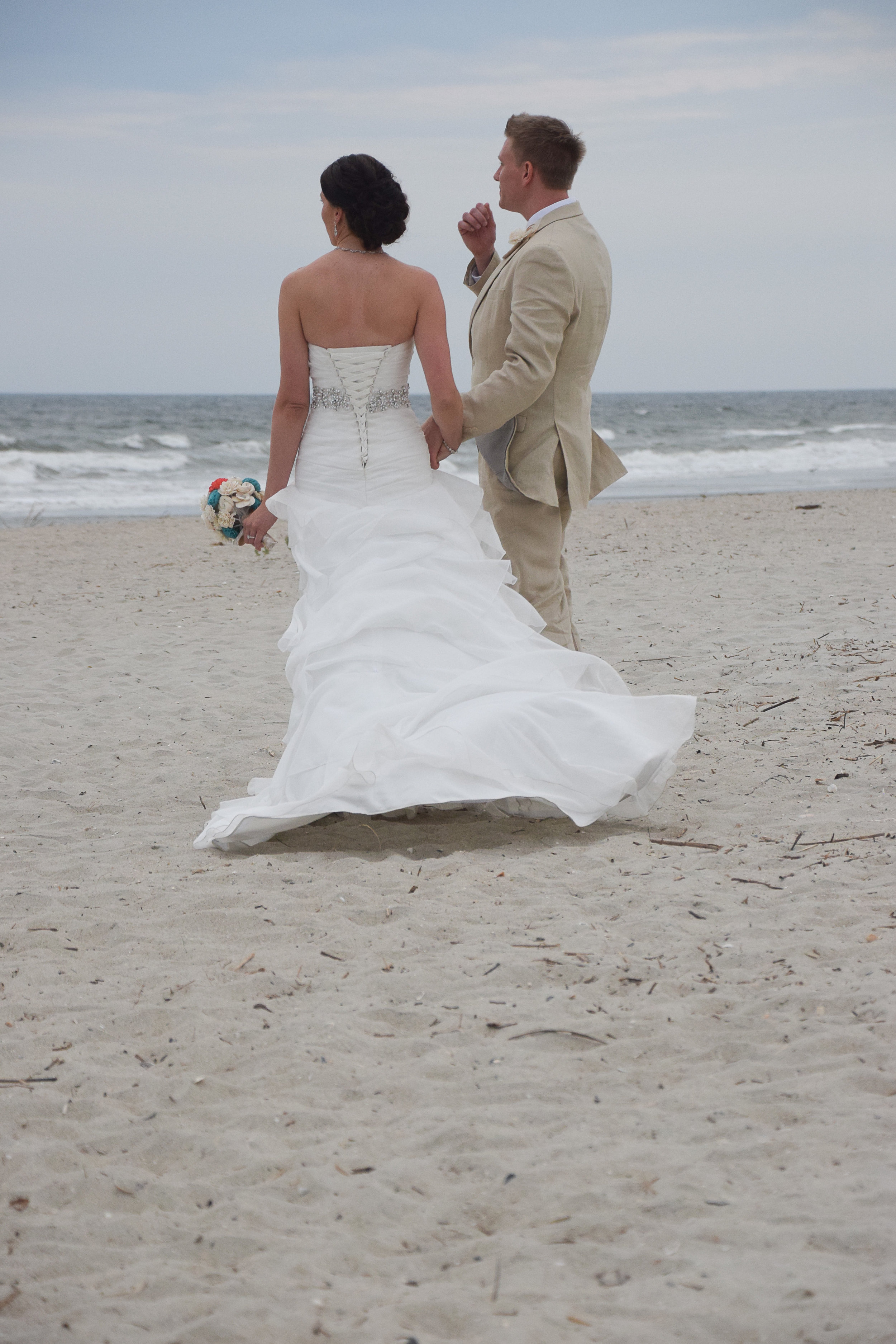 Bride and groom walking on the beach.