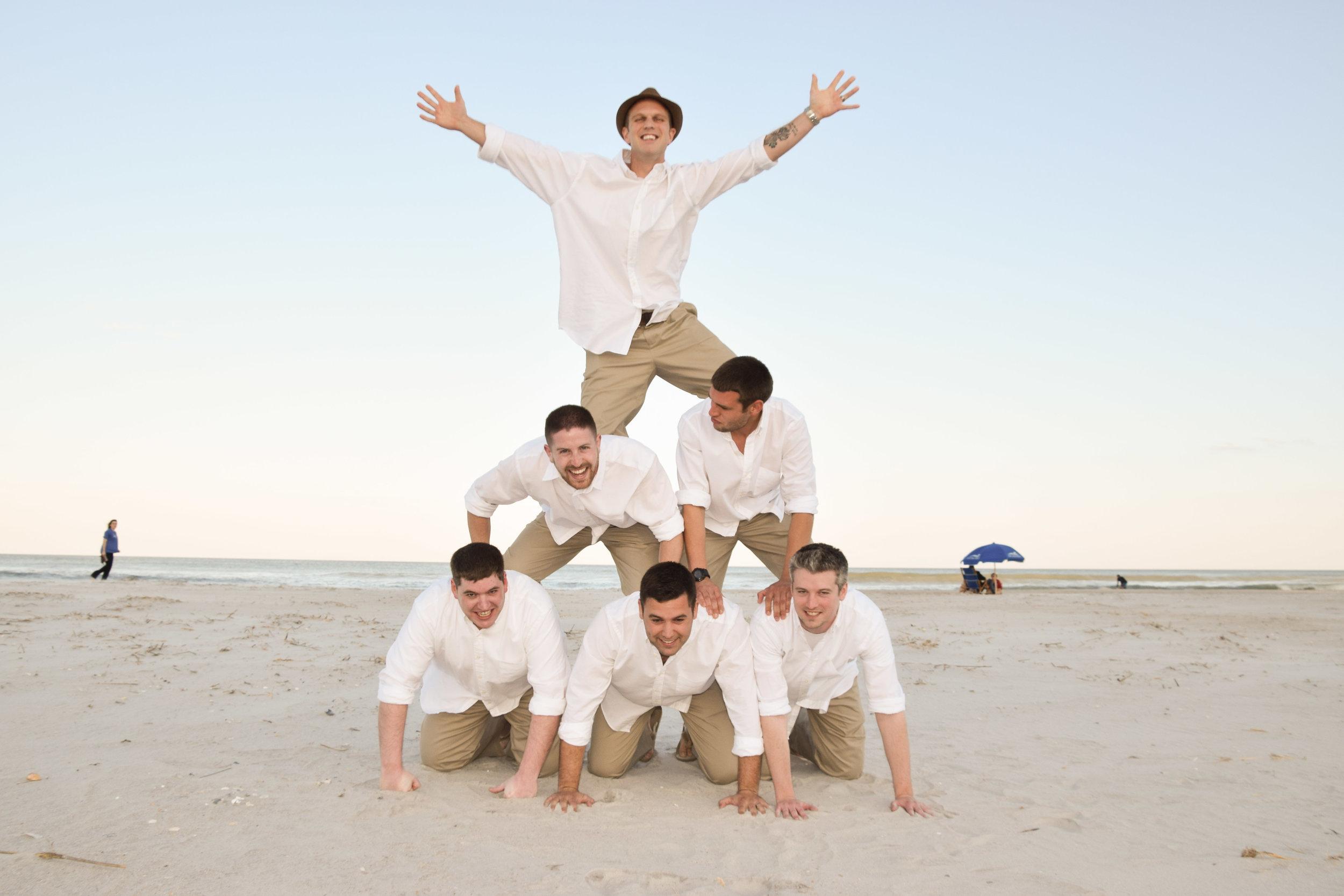 Groom and groomsmen make a pyramid on the beach.