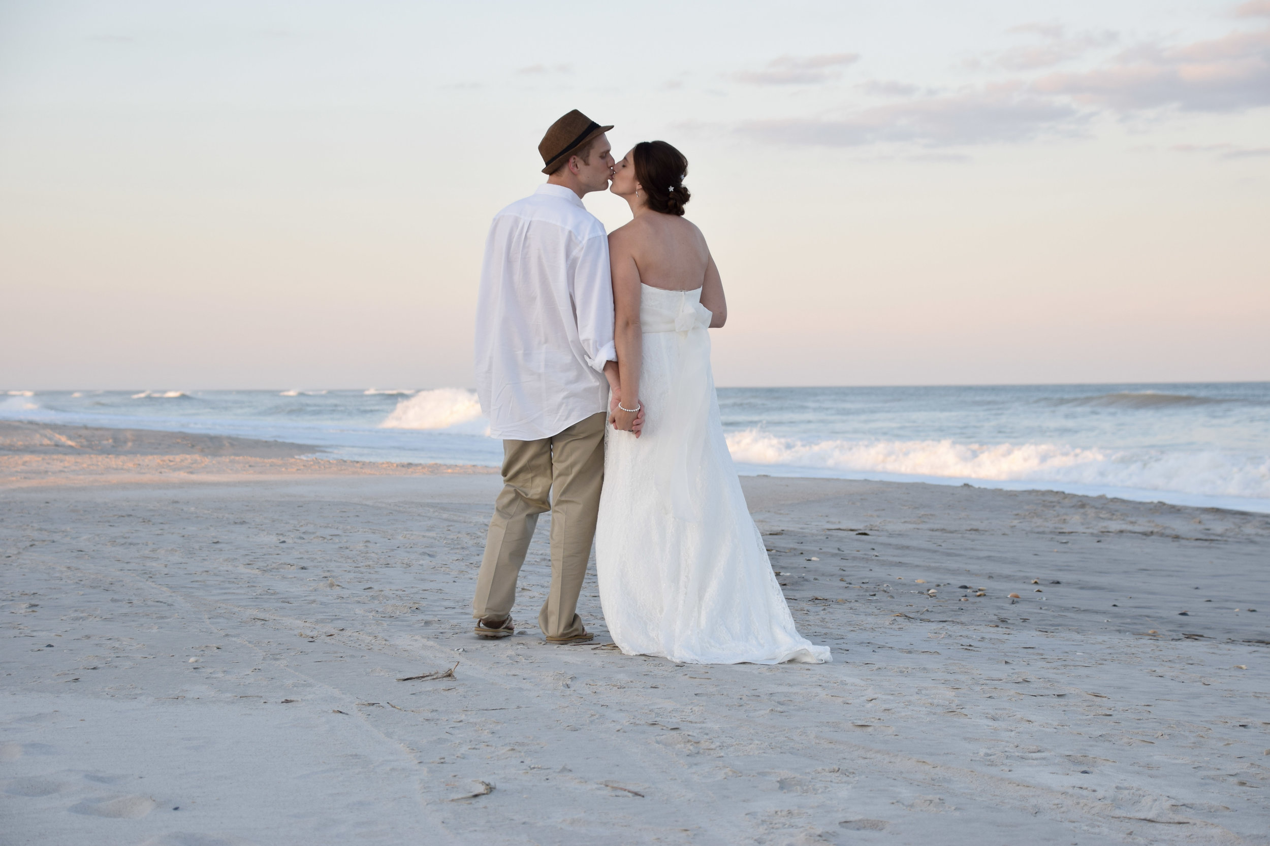 Bride and Groom walking on the beach pausing for a kiss.