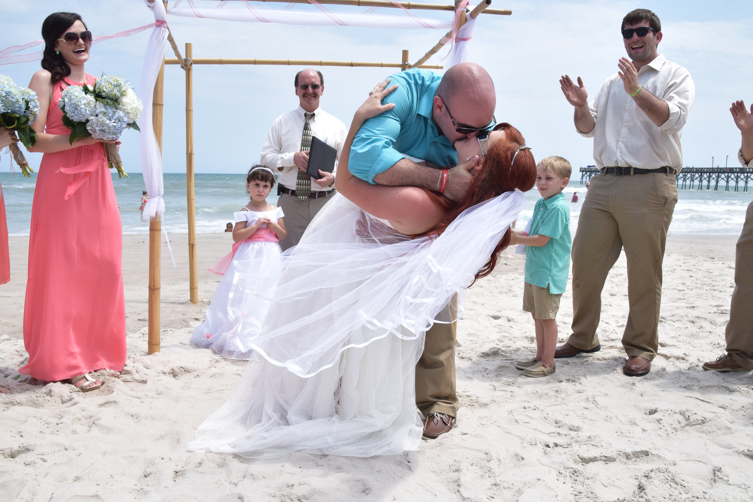 Bride and groom first kiss at alter on the beach.