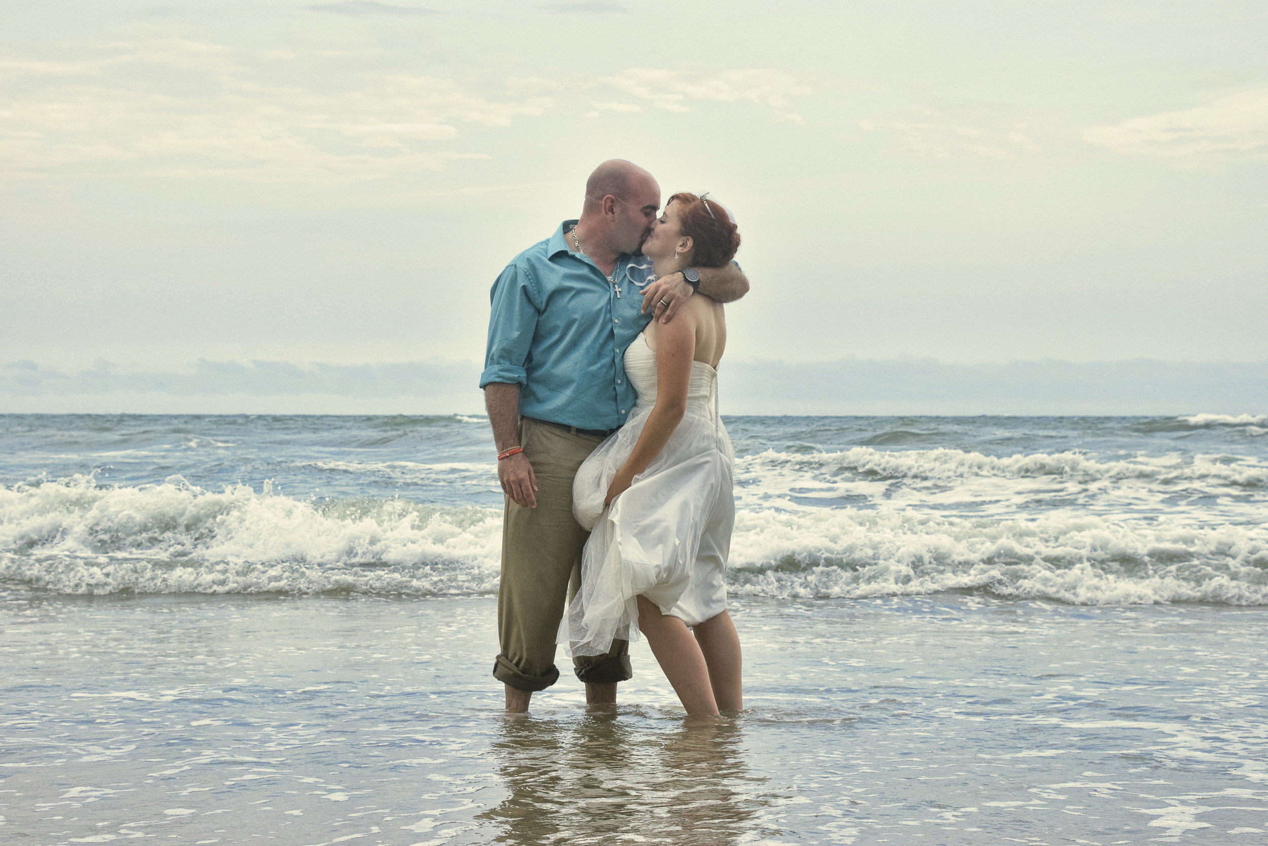 Bride and groom kissing while standing in the ocean.