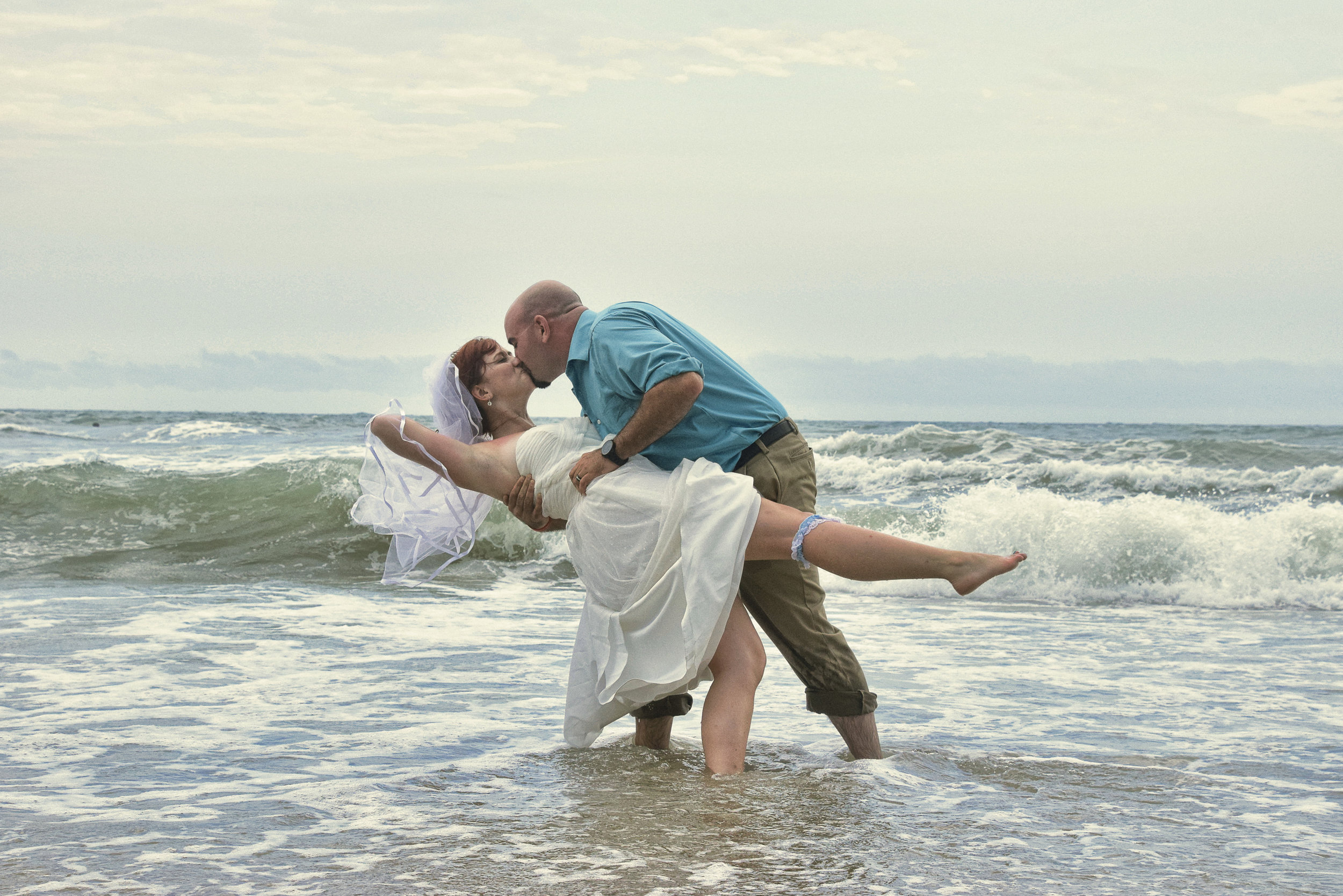 Groom dips his bride while standing in the ocean.