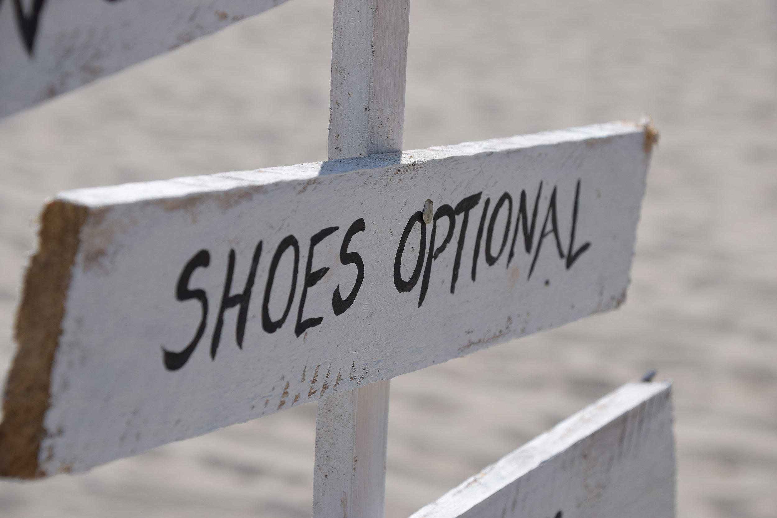 Shoes optional sign at entrance to beach wedding.