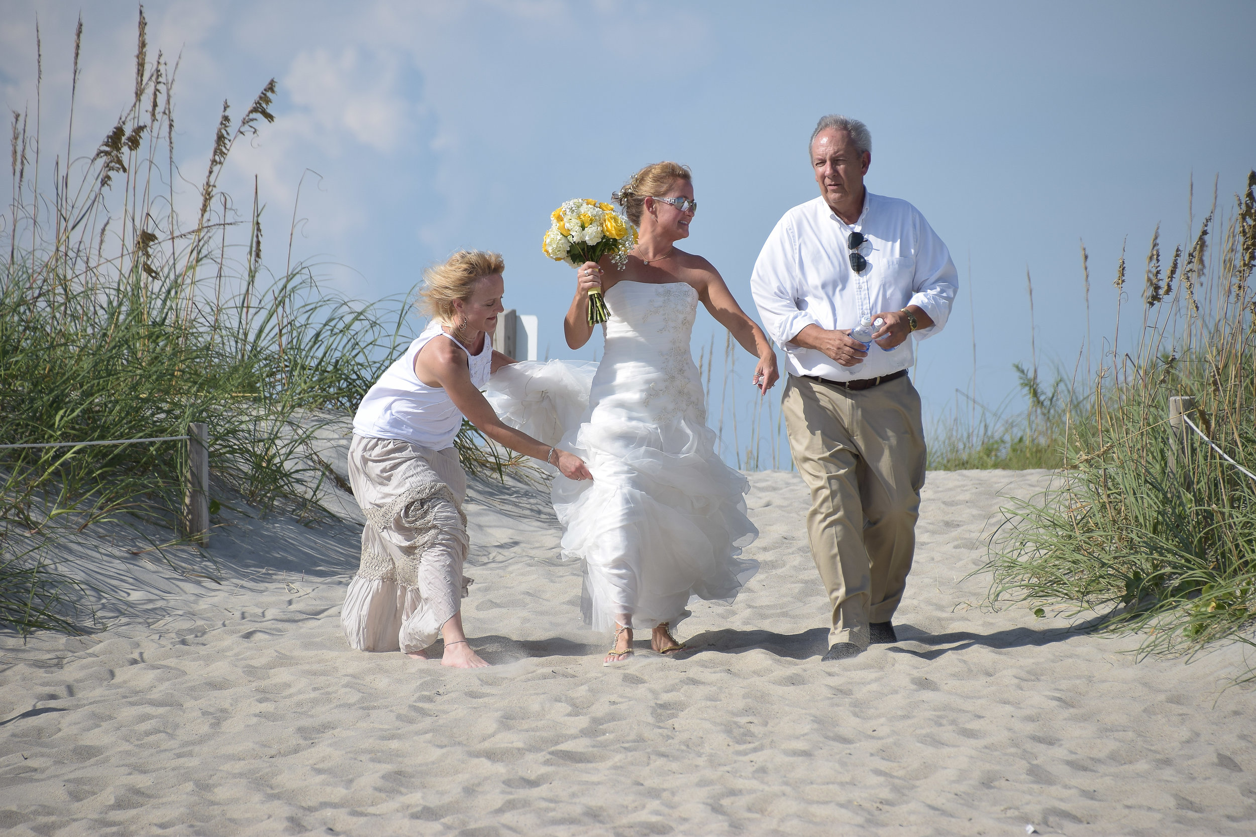 Bride walking down the aisle with dad while bridesmaid tries to fix her dress.