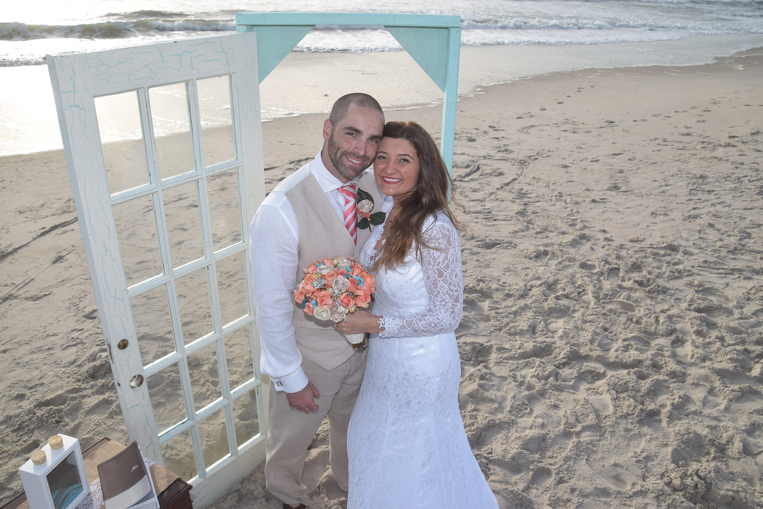 Newly married couple posing on the beach.