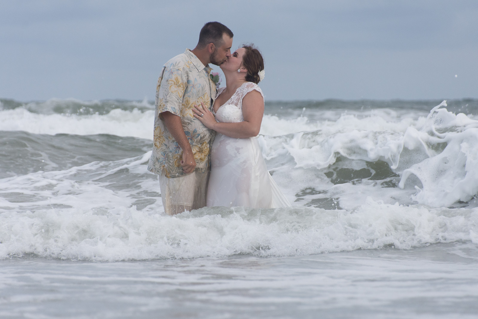 Bride and Groom kissing in surf.