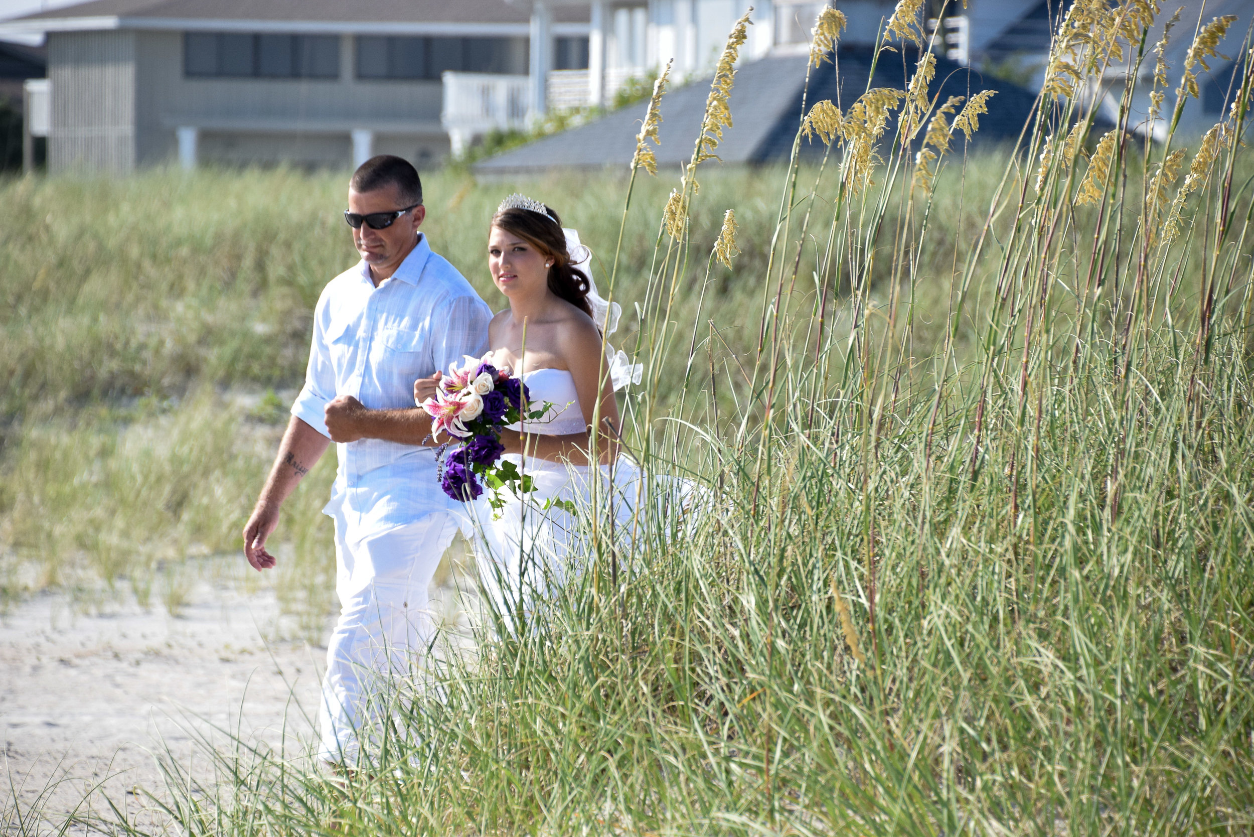 Bride being walked to her wedding by her dad.