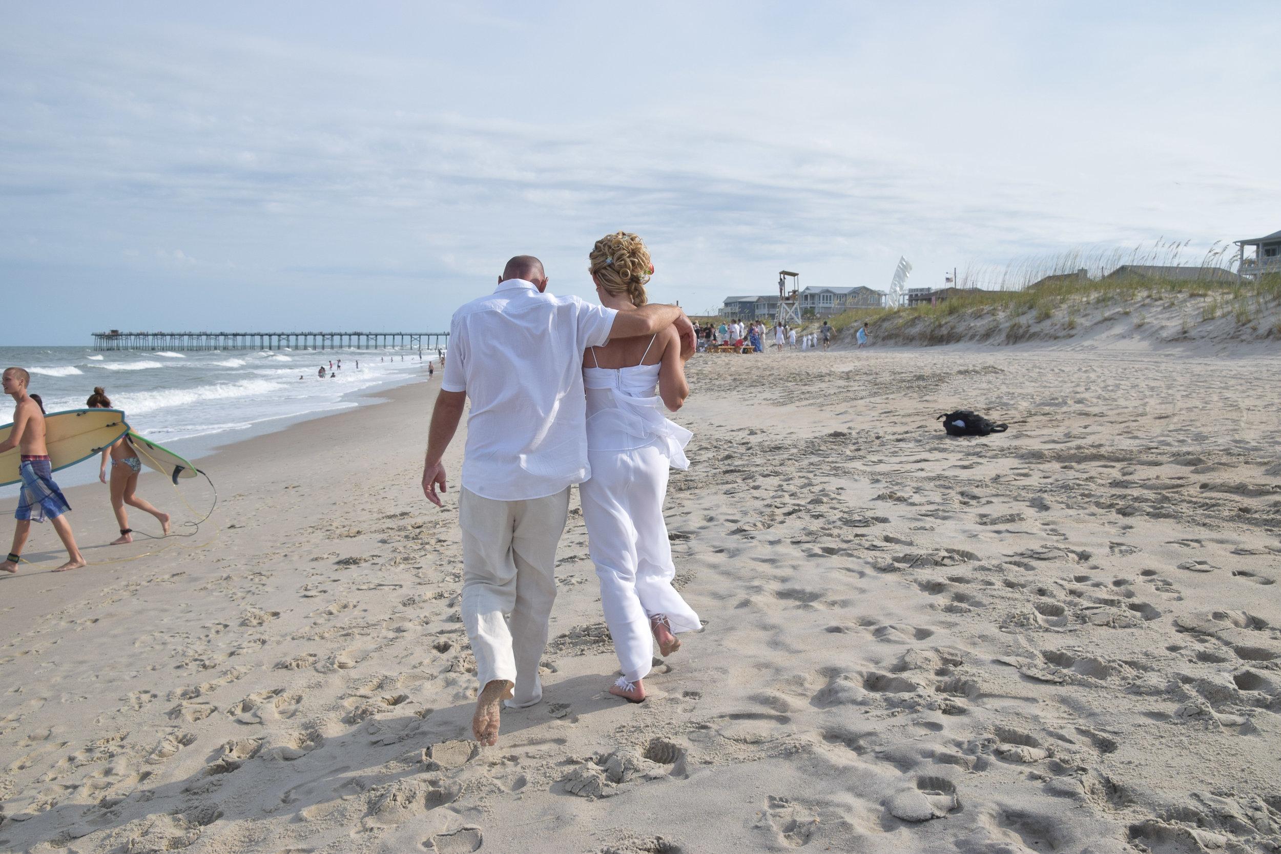 Bride and groom walking down the beach.