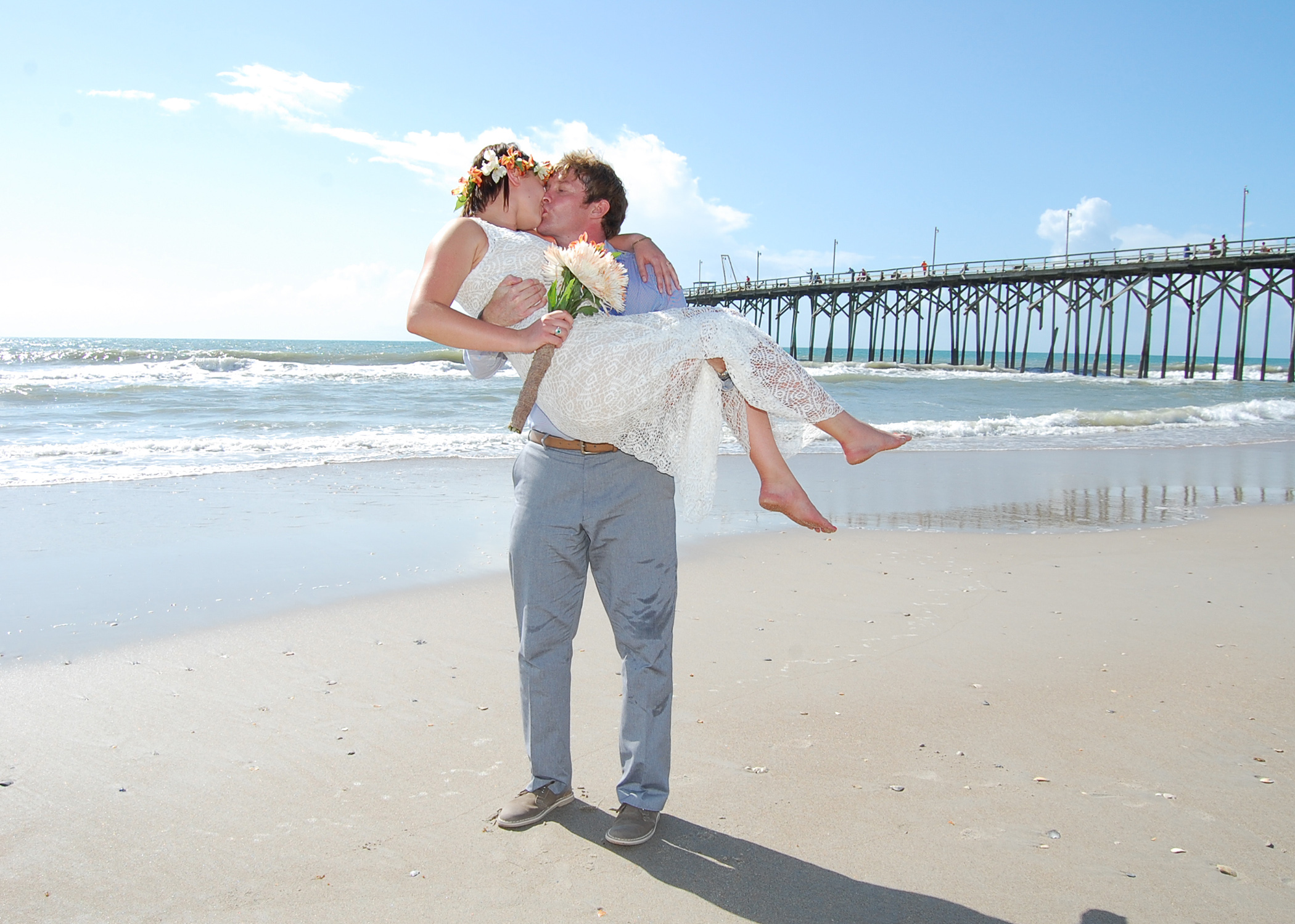 Wide Shot of Groom picking up bride on the beach.