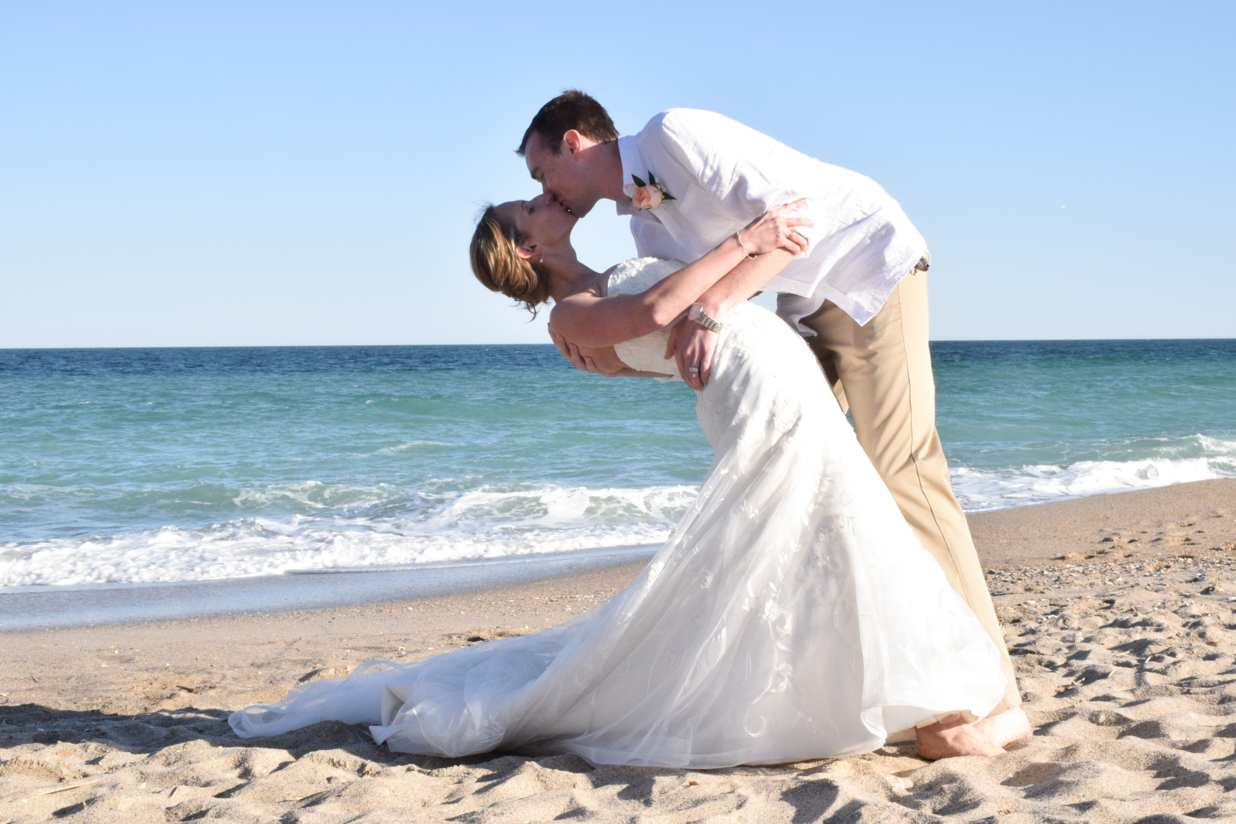 Groom dipping bride on beach.