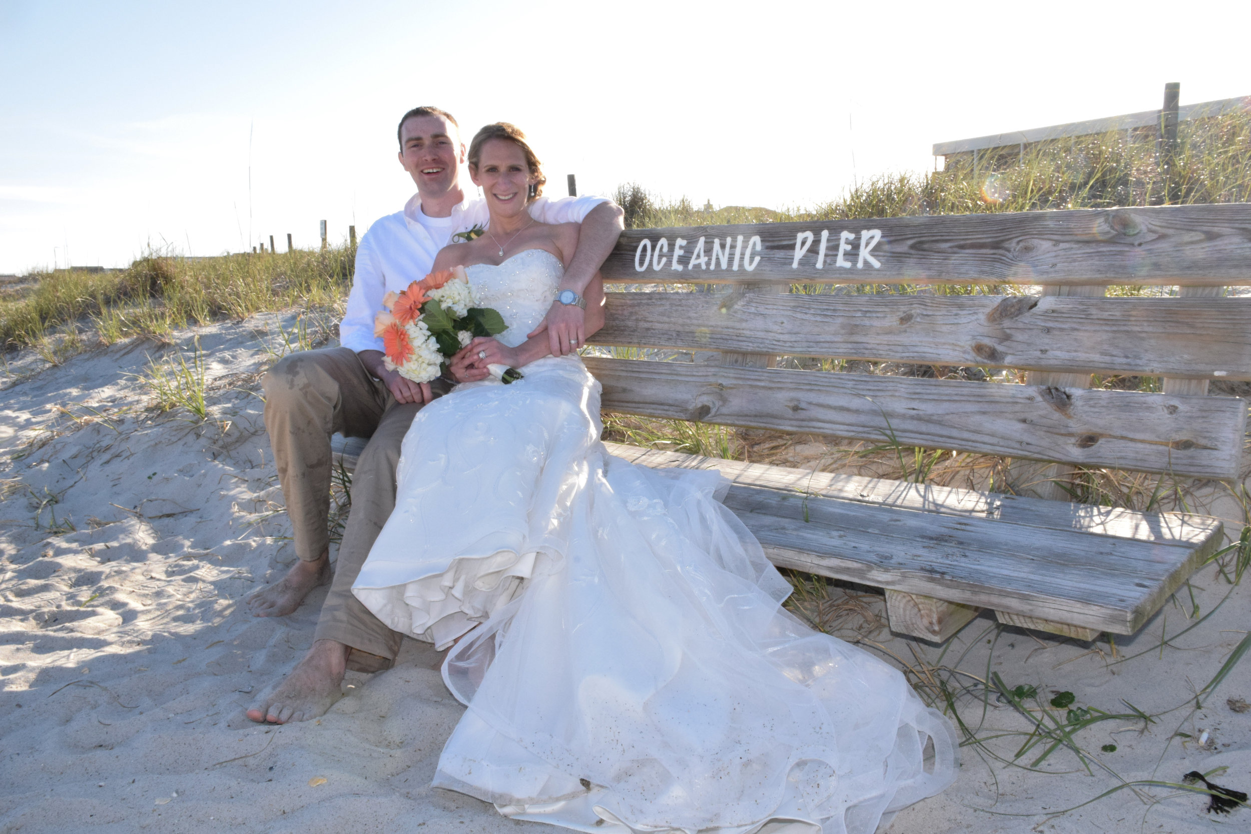 Bride and groom sitting on bench.