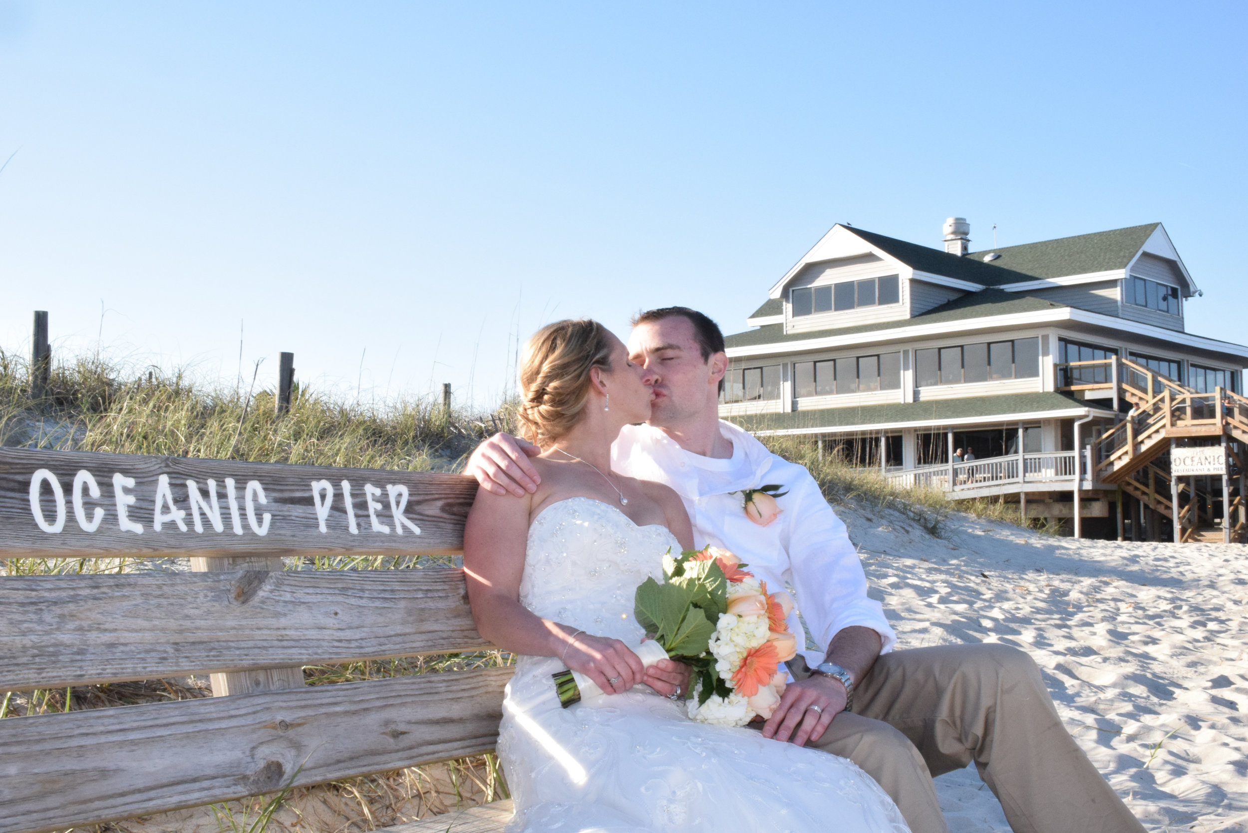 Newly married couple kissing on bench.