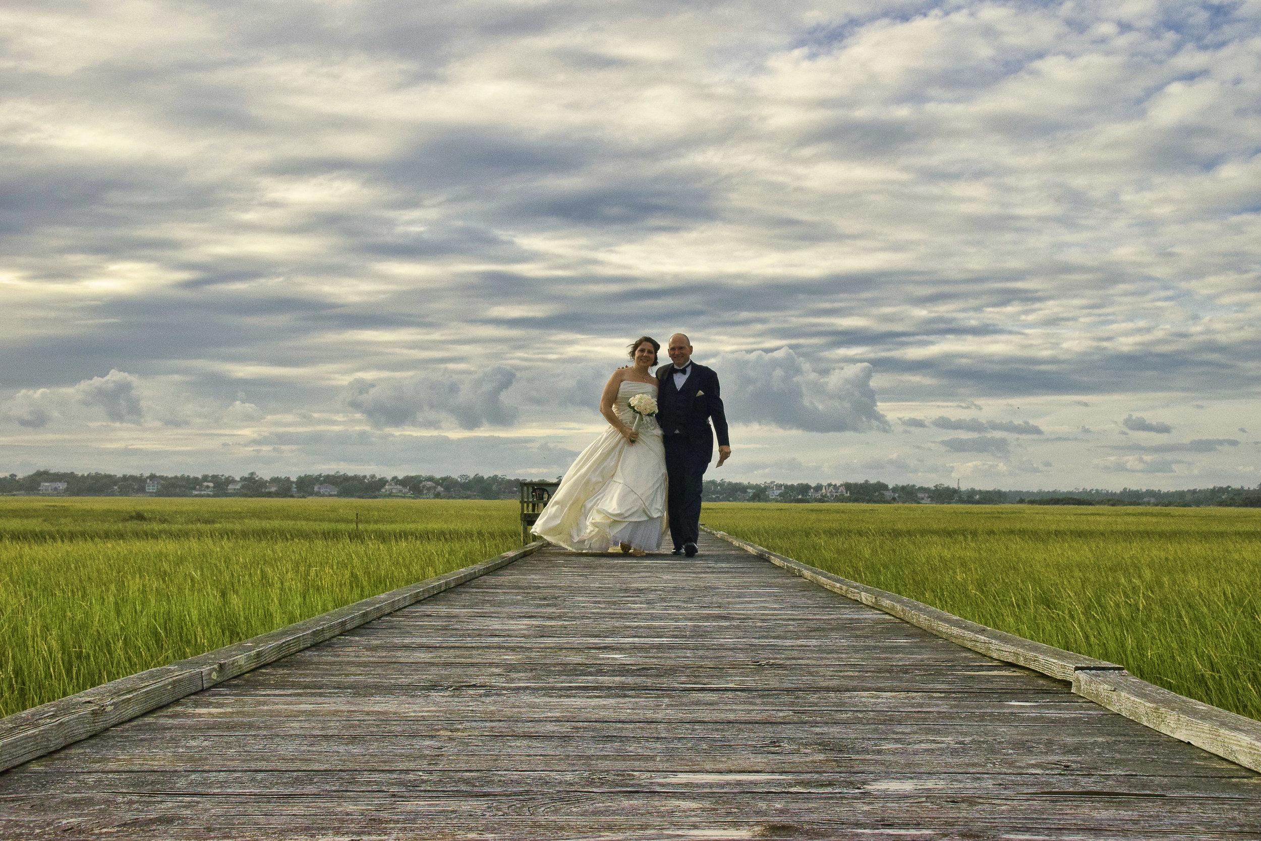 Bride and groom on boardwalk.