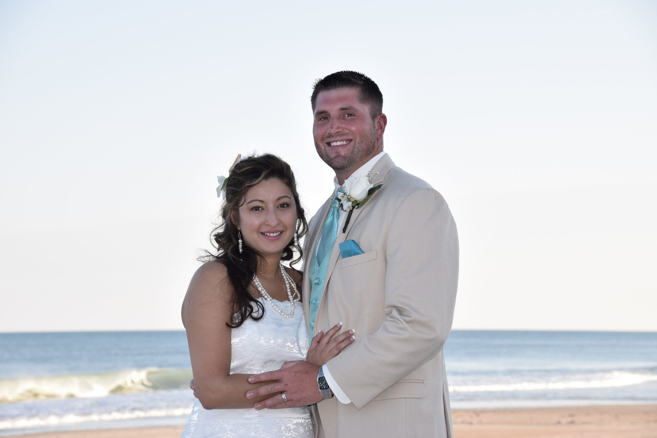 Bride and Groom posing on the beach.