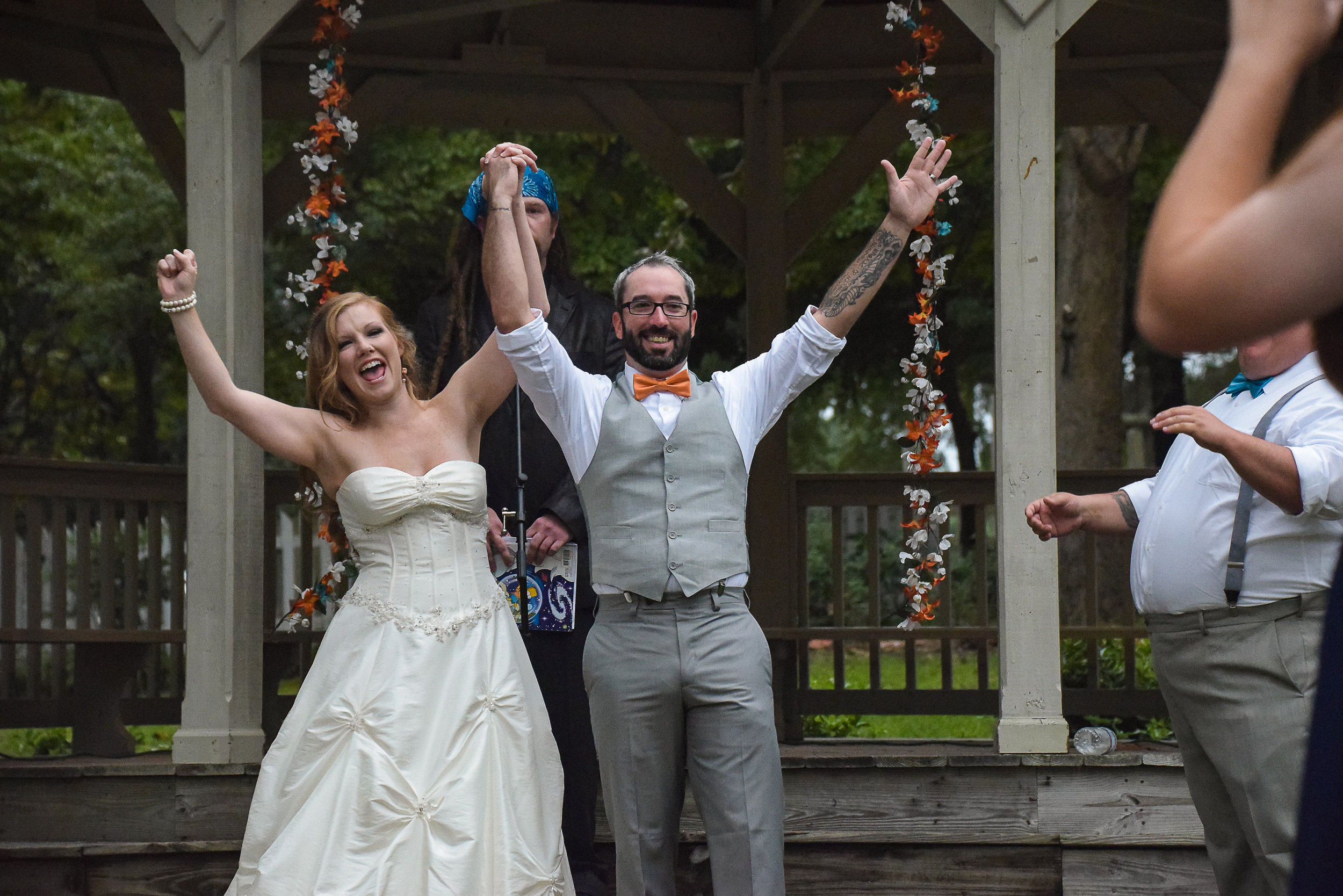 Bride and groom with arms raised.