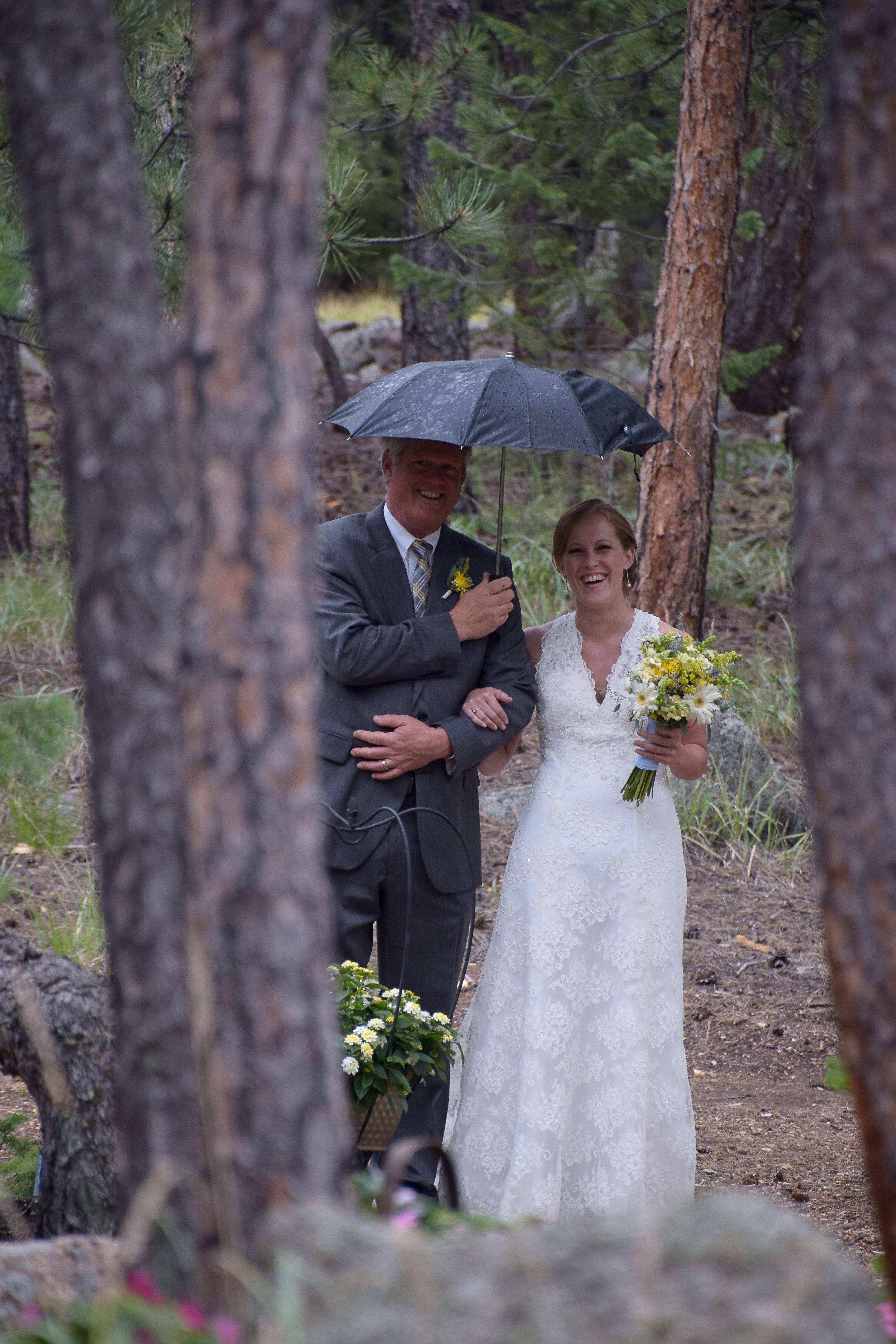 Dad walking bride to altar with umbrella.