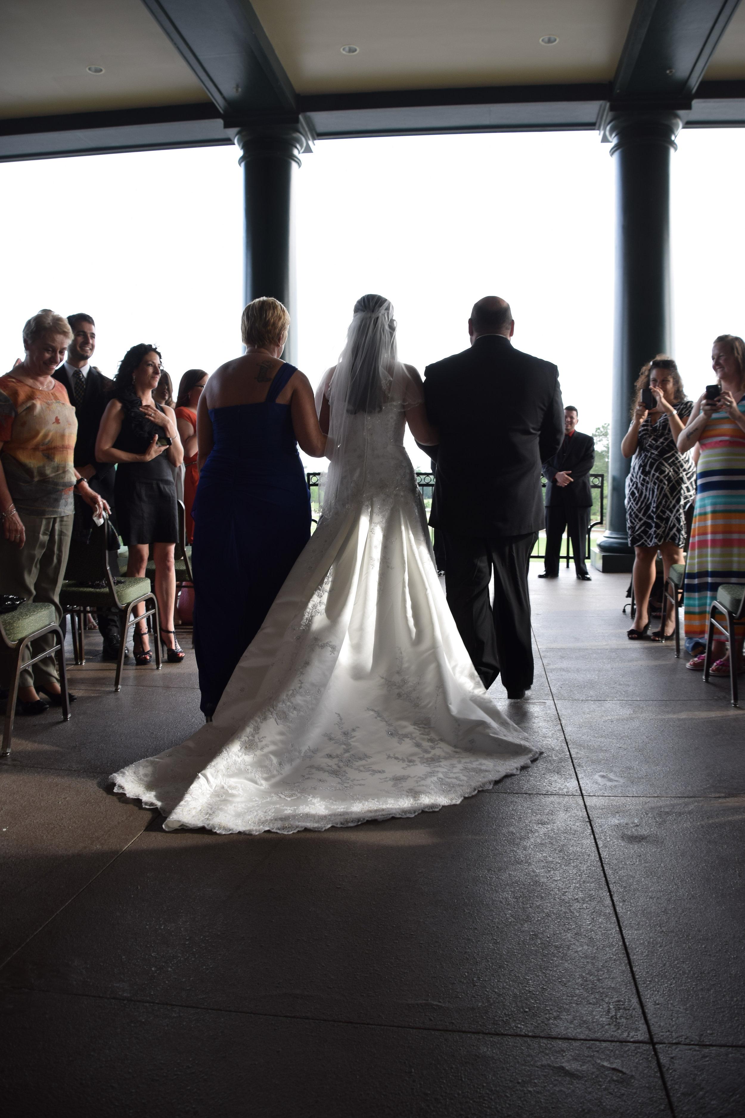 Parents walking bride down the aisle.