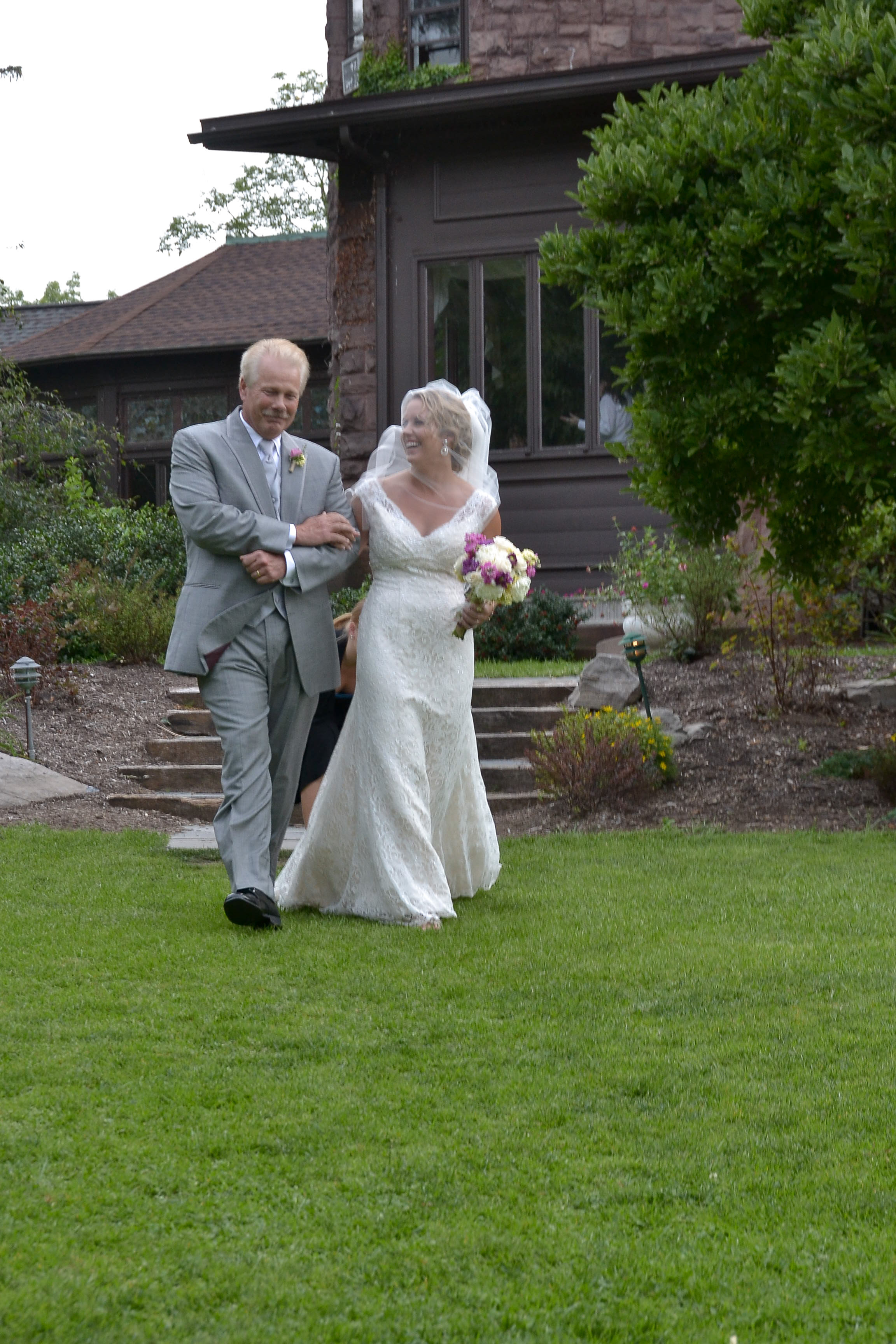 Bride with dad walking to wedding ceremony.