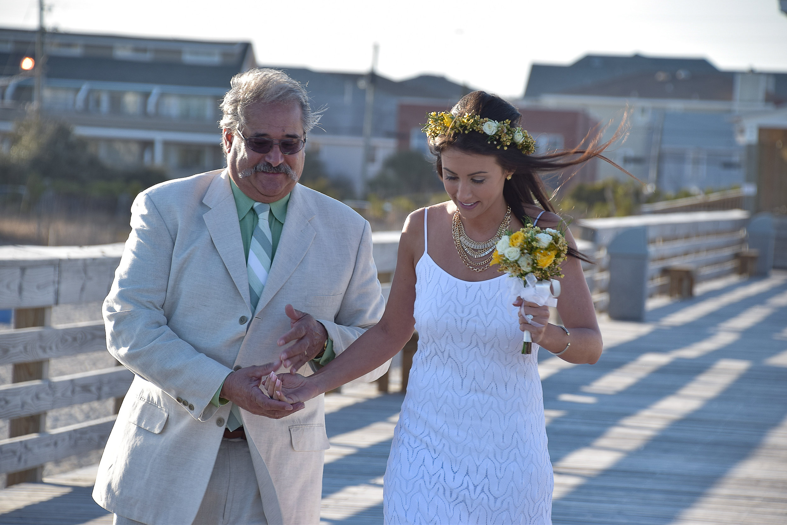 - Walking to the ceremony with her Dad on the Oceanic Pier in Wrightsville Beach, NC.