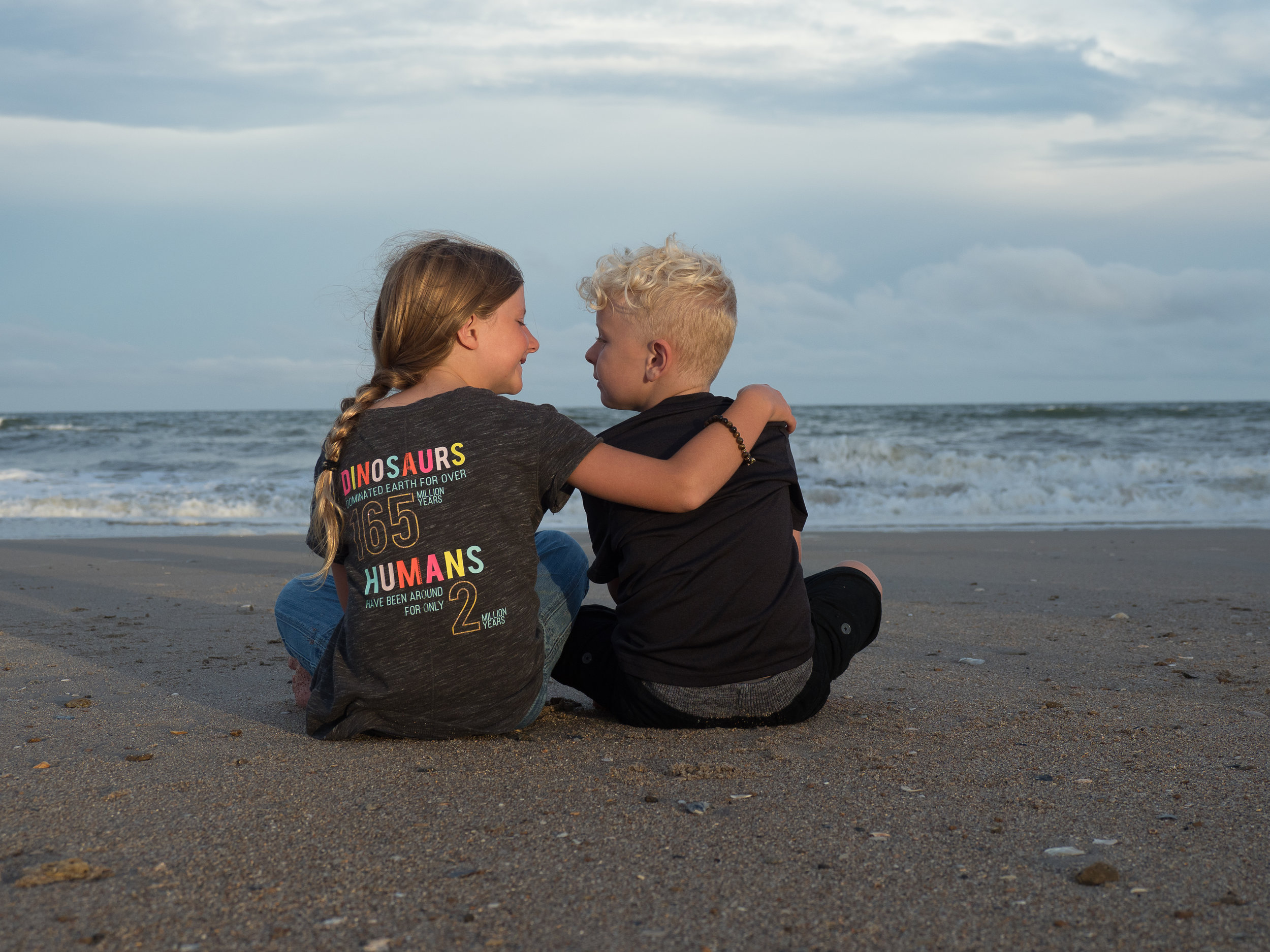 - Brother and sister sitting on beach looking at each other with ocean in the background. North Topsail Beach, NC.